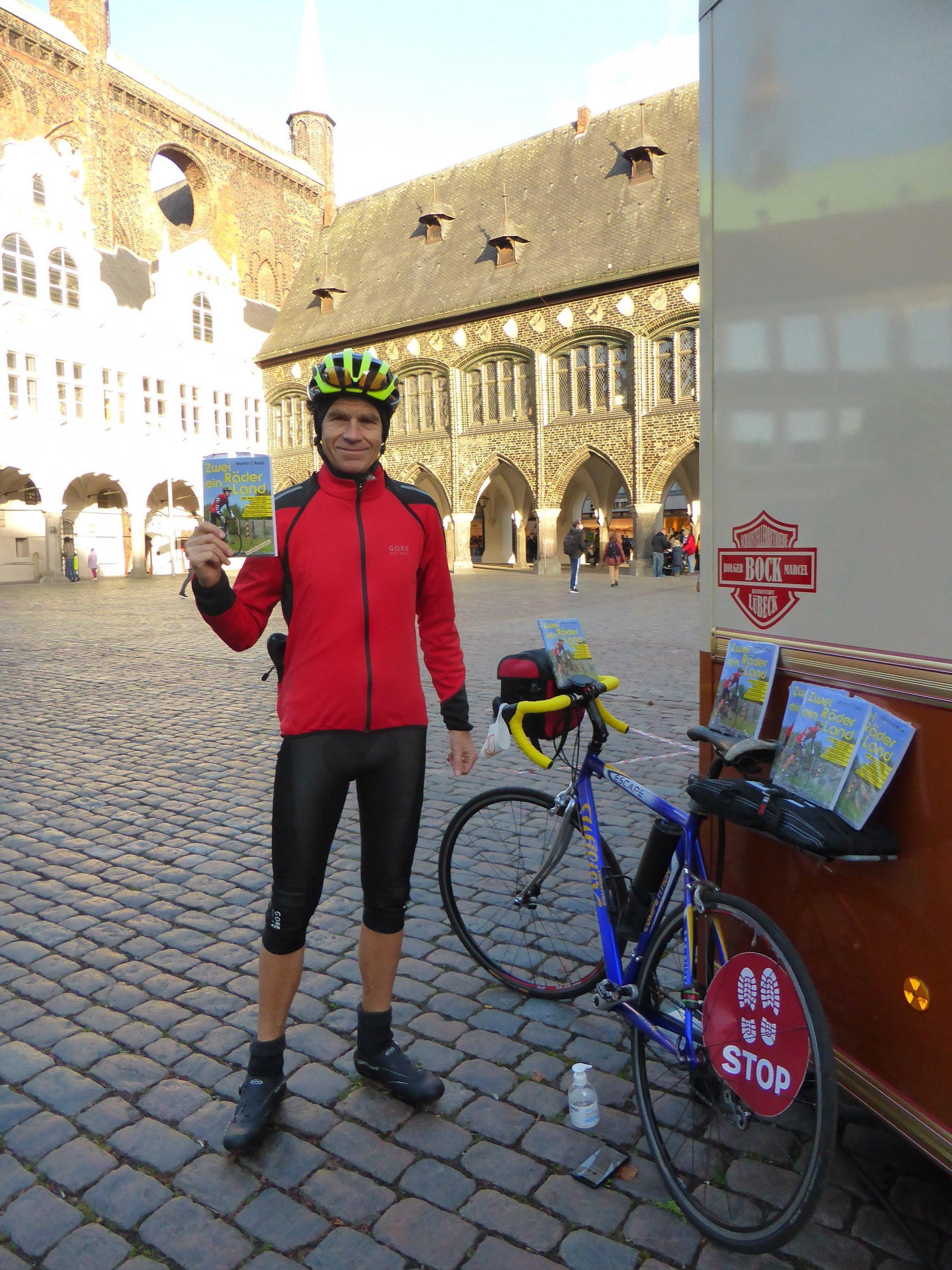 """Martin C Roos steht in Radlerkluft neben seinem Rennrad, in der Rechten ein Exemplar seines Buchs """"Zwei Räder, ein Land""""."""