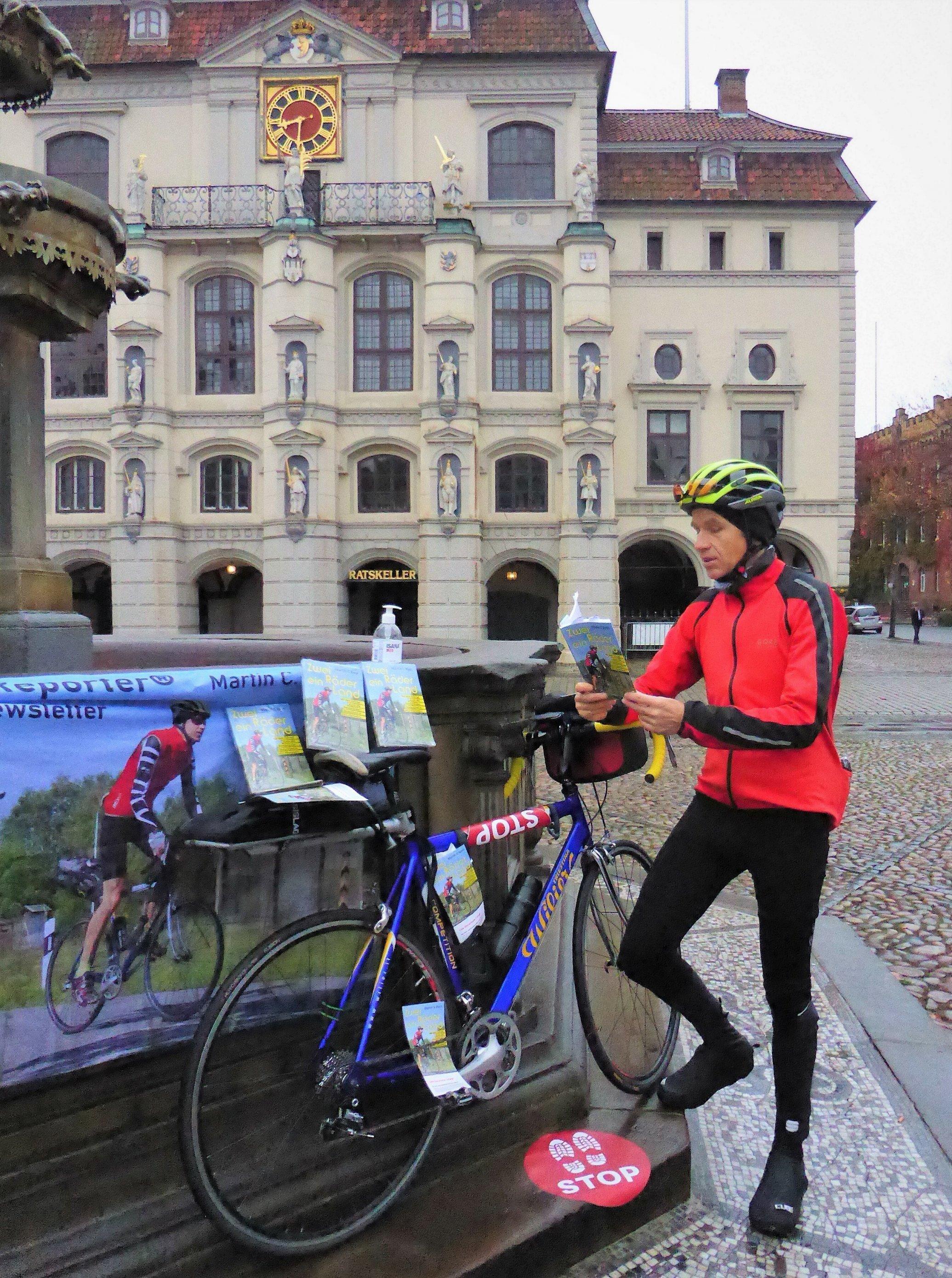 Während das Rennrad am Marktbrunnen ruht, liest der RadelndeReporter vor dem Hintergrund des Rathauses aus seinem Buch.