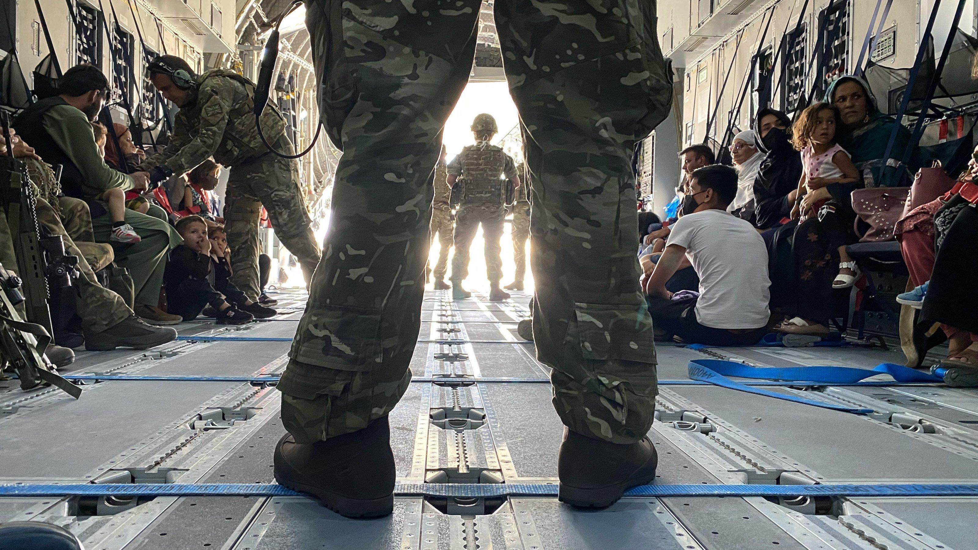 Blick in den Laderaum einer britischen Militärmaschine, im Vordergrund die Beine eines breitbeinig stehenden Soldaten in Tarnuniform. Im Hintergrund zivile Personen, die auf dem Boden des Flugzeuges sitzen.