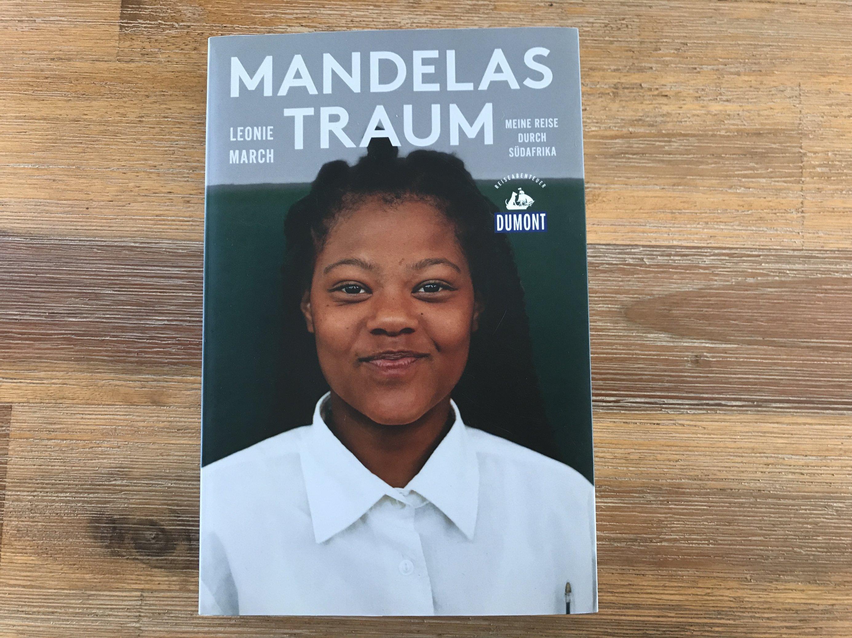 """Ein Buch liegt auf hölzernem Grund. Das Cover zeigt die Überschrift """"Mandelas Traum"""". Darunter lacht ein Mädchen in die Kamera."""