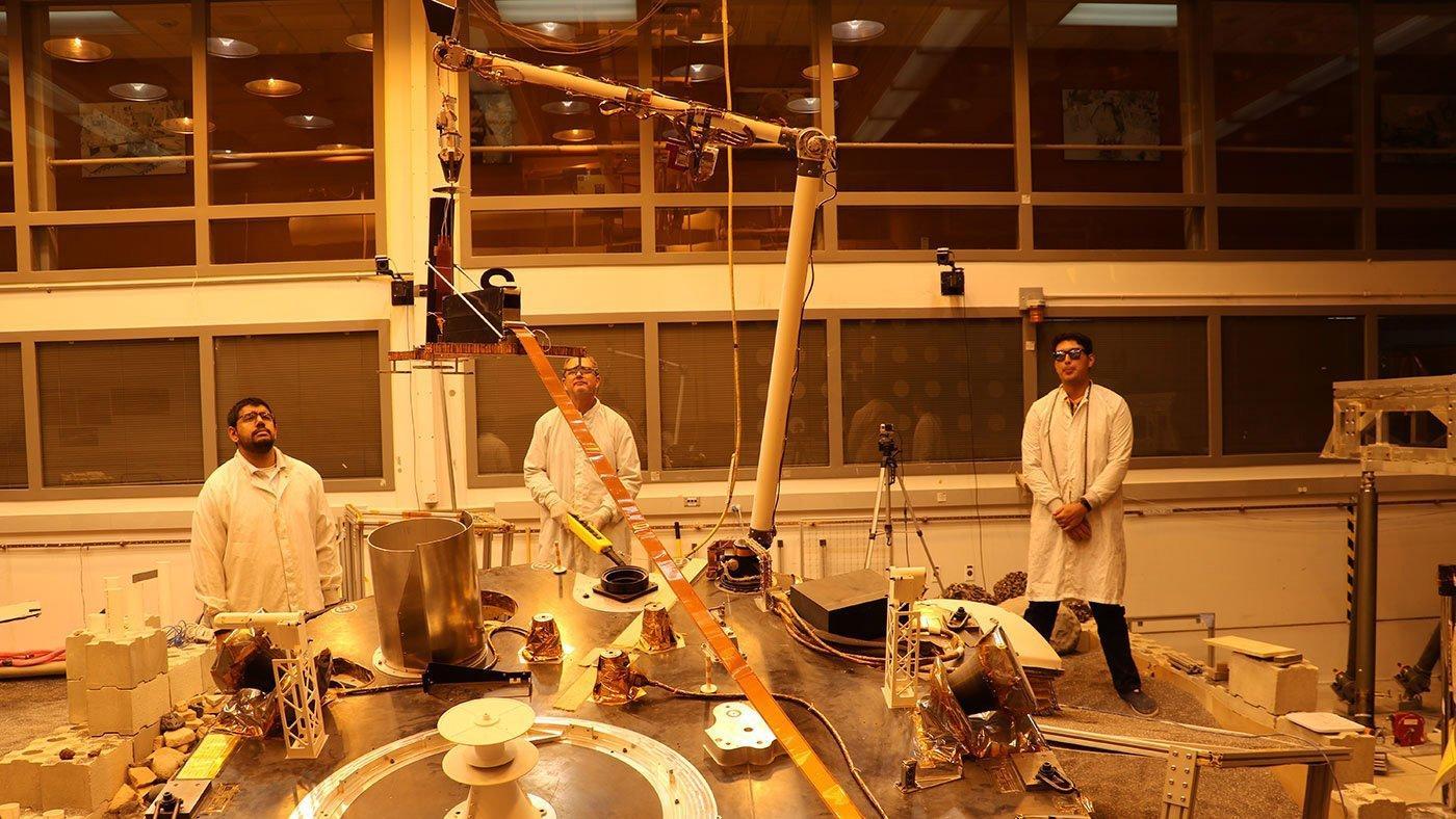 Ein Roboterarm in einem Labor auf der Erde hebt die Wärmesonde in die Höhe, während drei Forscher zusehen