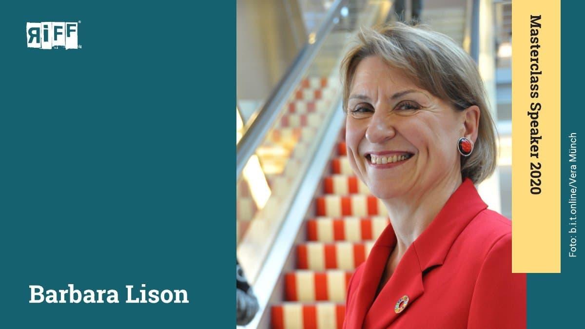 Eine Dame mit rotem Ohrring lächelt in die Kamera. Hinter ihr ist eine rot-weiß gestreifte Rolltreppe zu sehen.