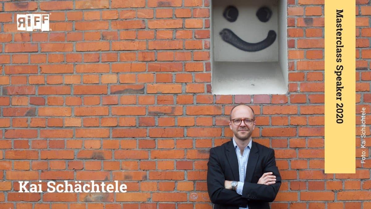 Ein Mann mit Brille steht vor einer roten Ziegelmauer. Über ihm ist die Mauer weiß und trägt ein mit Sprühfarbe aufgemalten Smiley.