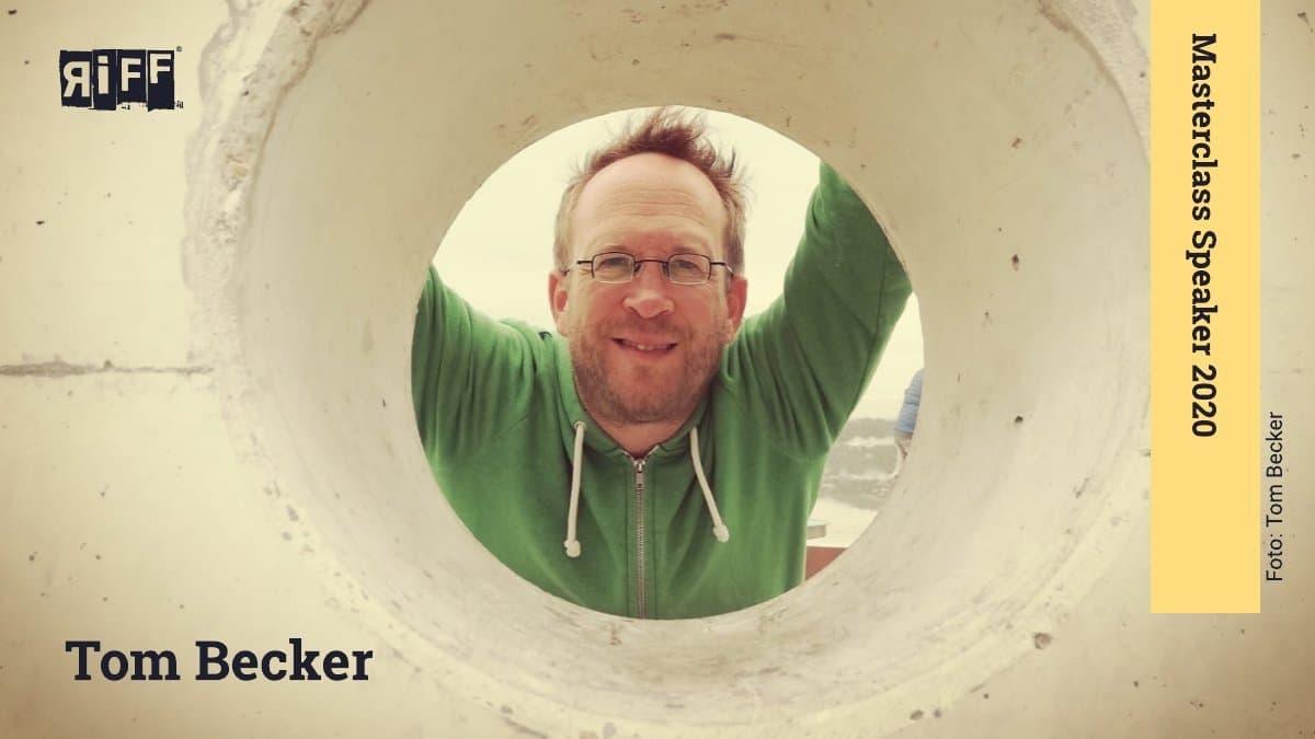 Ein Mann mit Brille schaut durch die Öffnung eines Rohrs.