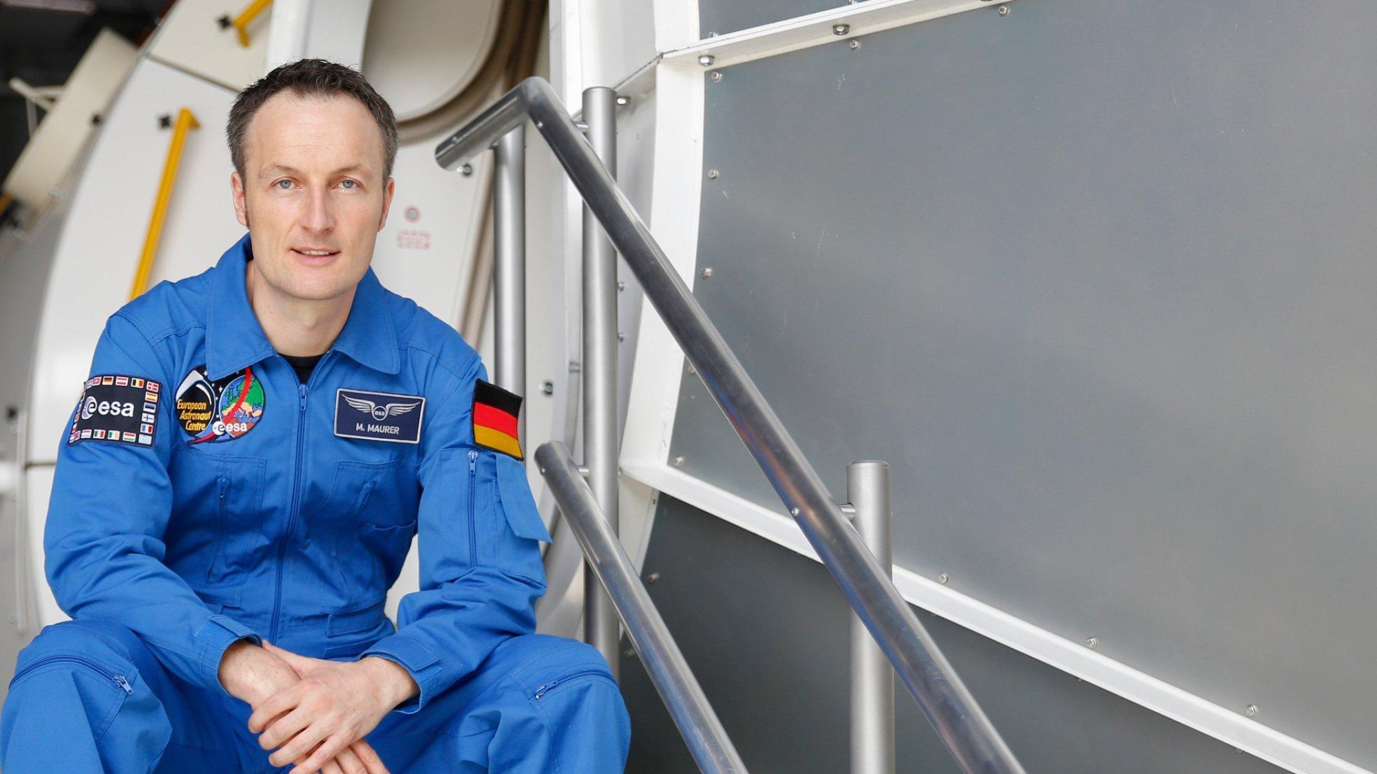 Der Astronaut Matthias Maurer sitzt in blauem Anzug auf einer Treppe vor dem Columbus-Modul