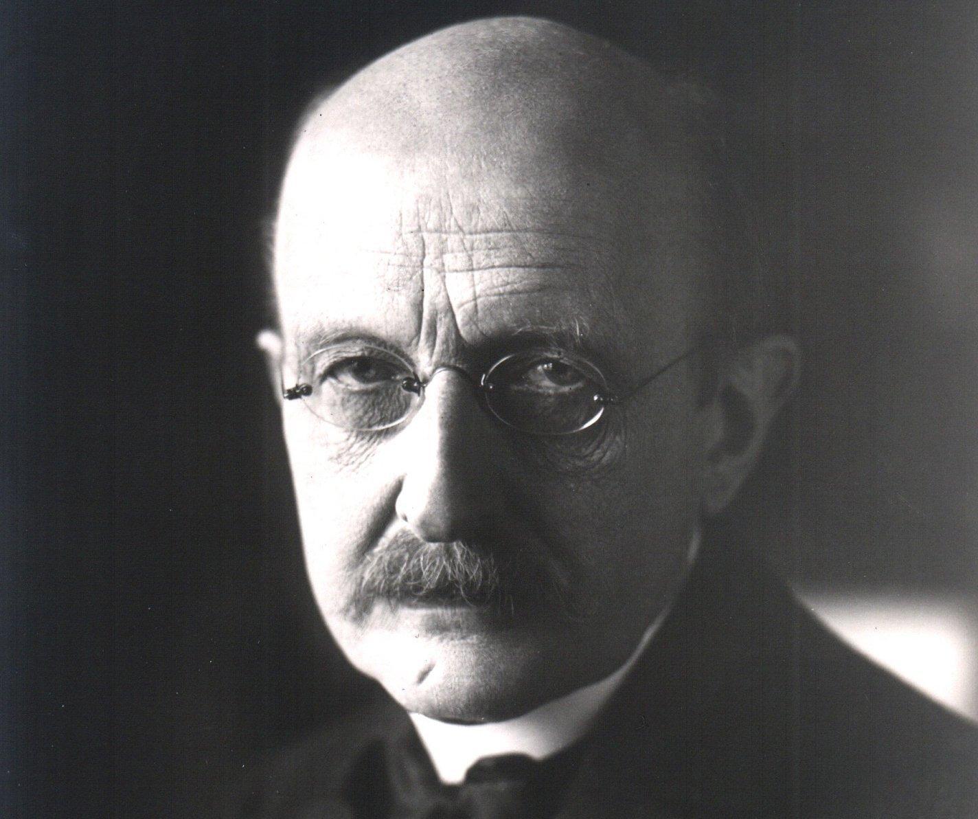 Zu sehen ist ein schwarzweißes Porträtfoto des Physikers Max Planck, der – von links beleuchtet – den Betrachter mit festem Blick durch seine Nickelbrille ansieht. Planck lebte von 1858bis 1947und begründete im Jahr 1900die Quantentheorie. Damit löste er in der Physik eine Revolution aus. Zwischen Religion und Naturwissenschaft sah der Physiker keinen Widerspruch. Für ihn waren es zwei unterschiedliche Ebenen der Wirklichkeit: Die eine beschrieb die objektiven Vorgänge in der realen Welt, während die andere, die christliche Religion, für die Grundlagen der Ethik sorgte