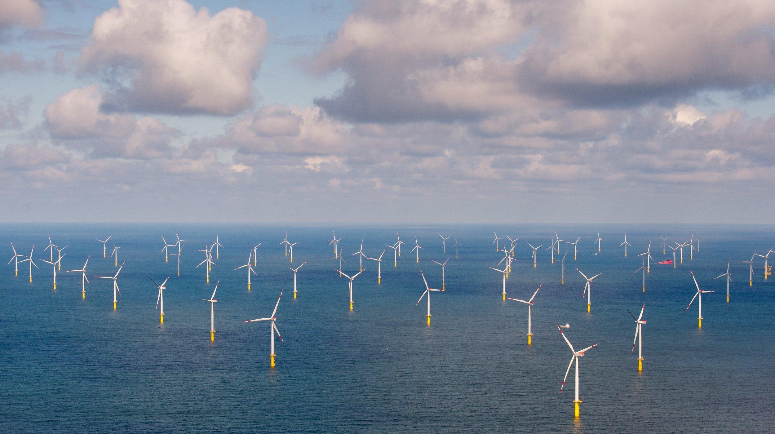 Windräder stehen in Reih und Glied im Meer bei Sylt