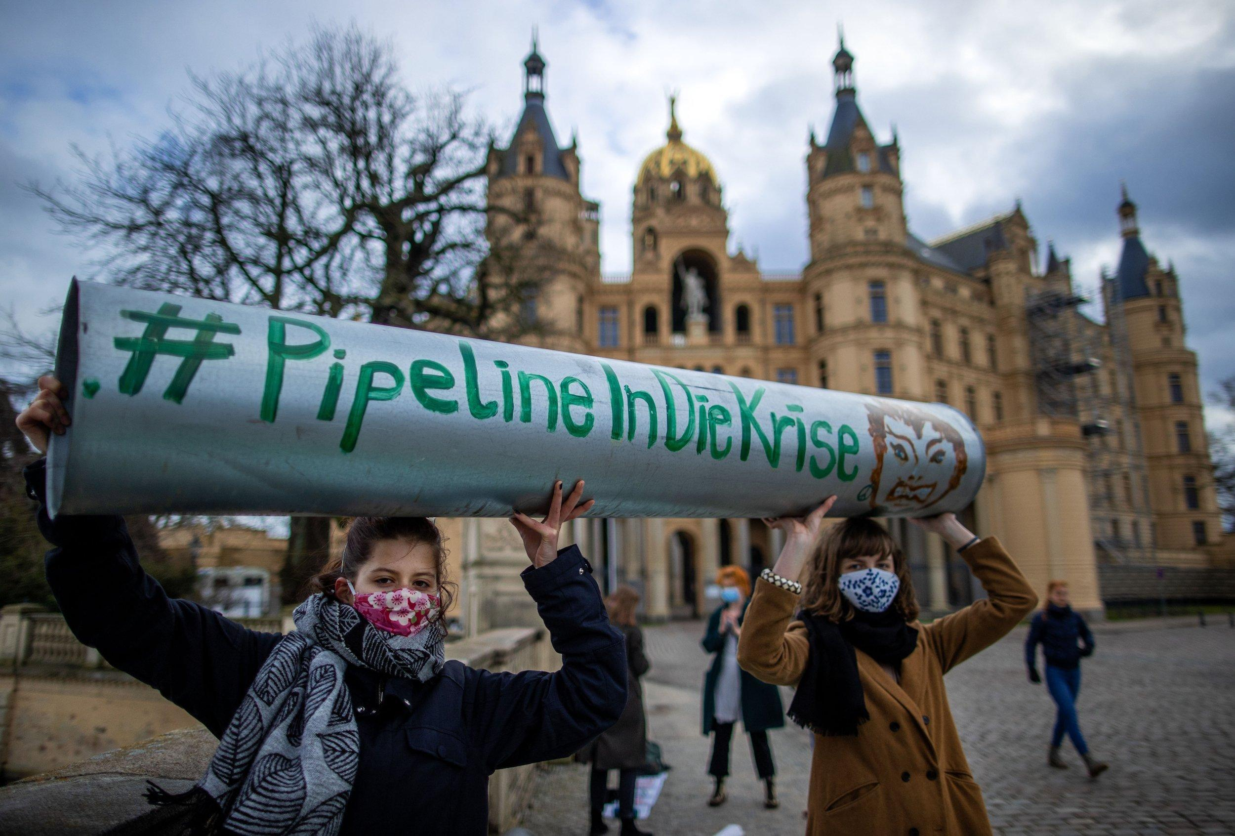 """Zwei junge Frauen halten ein Stück symbolische Pipeline mit der Aufschrift """"Pipeline in die Krise"""" vor den Landtagssitz im Schweriner Schloss in die Höhe."""