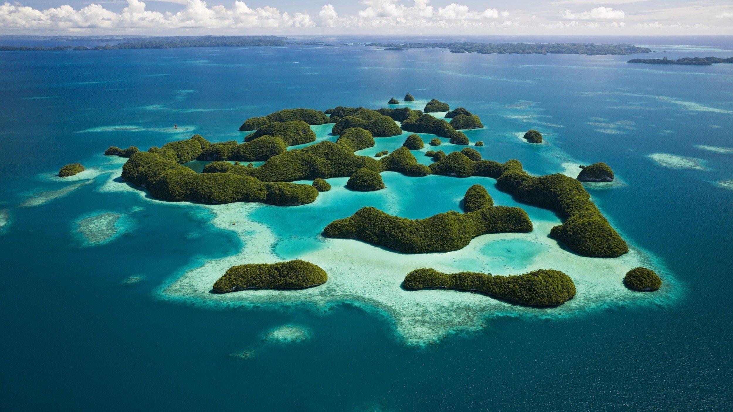 Zu sehen ist ein Luftbild von 70kleinen Inseln des Pazfikarchipels Palau, umgeben von azurblauem Meer. 78Prozent der Ausschließlichen Wirtschaftszone stehen unter strengem Schutz