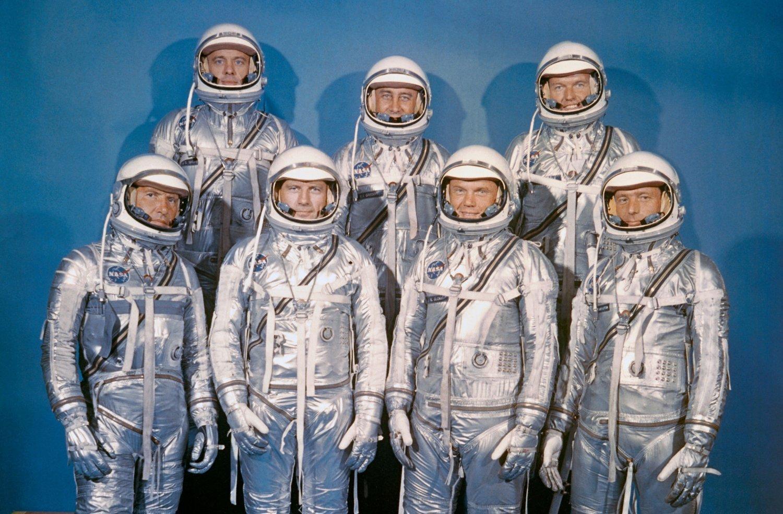 """Die Mercury 7, sieben Astronauten in silbrigen Anzügen posieren vor blauer Leinwand: Walter Schirra, Donald """"Deke"""" Slayton, John H. Glenn, Scott Carpenter; hintere Reihe: Alan B. Shepard, Virgil I. """"Gus"""" Grissom und Gordon Cooper"""