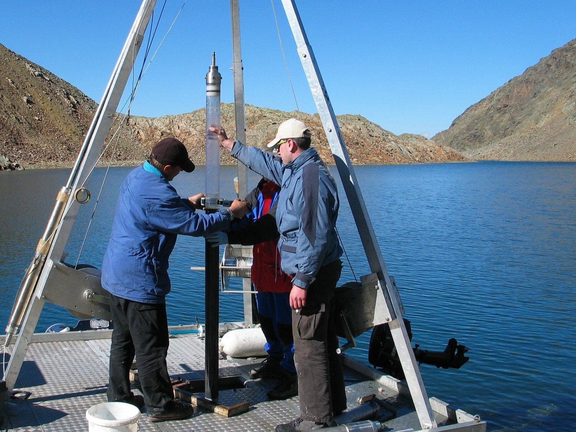 Unter einem Alugestänge hantieren drei Forscher auf einer schwimmenden Plattform mit einem übermannshohen Probenrohr.