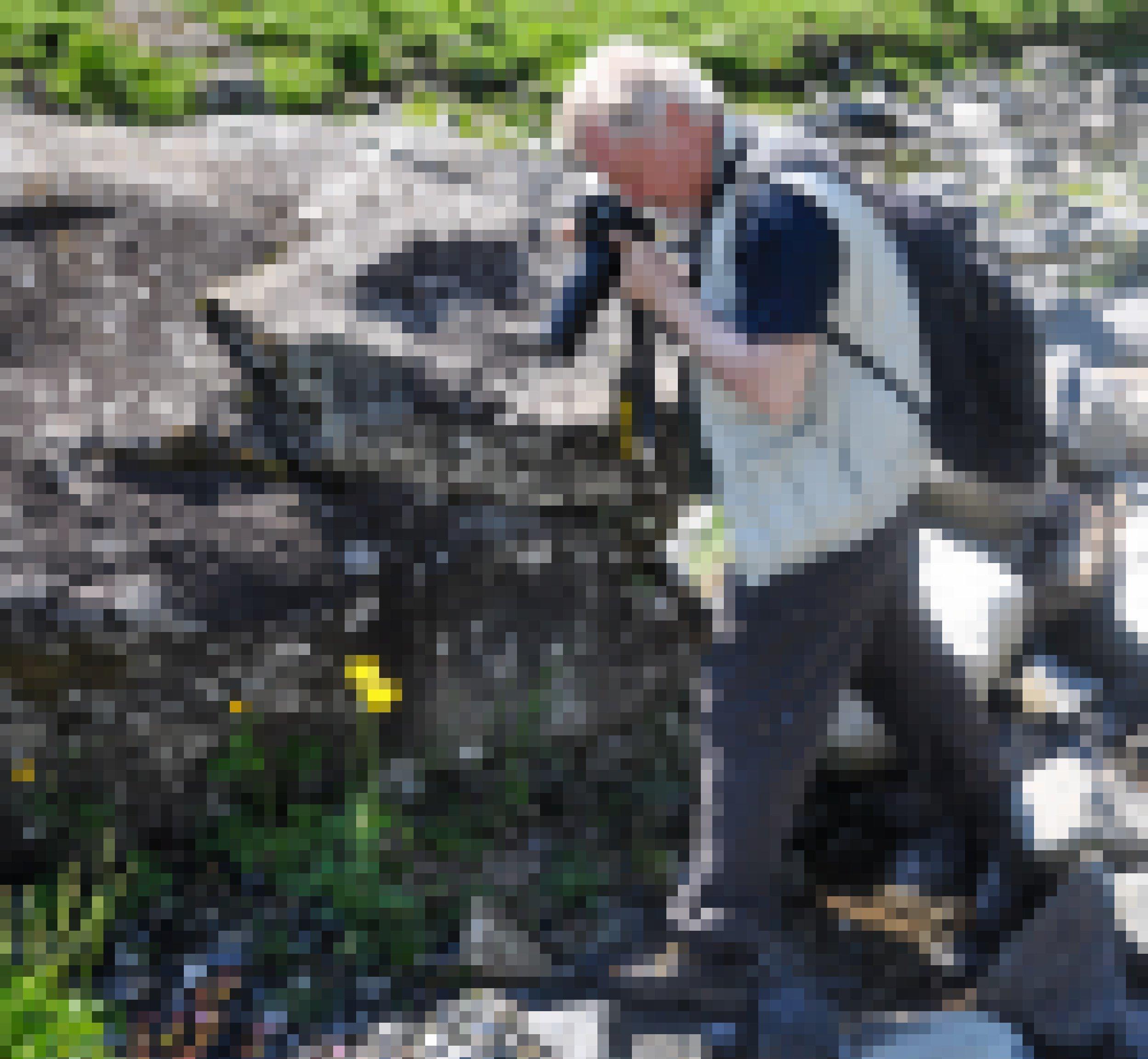 Ein Mann mit weißen Haaren und Bart fotografiert mit einem langen Objektiv eine gelbe Blüte in einer Felslandschaft.