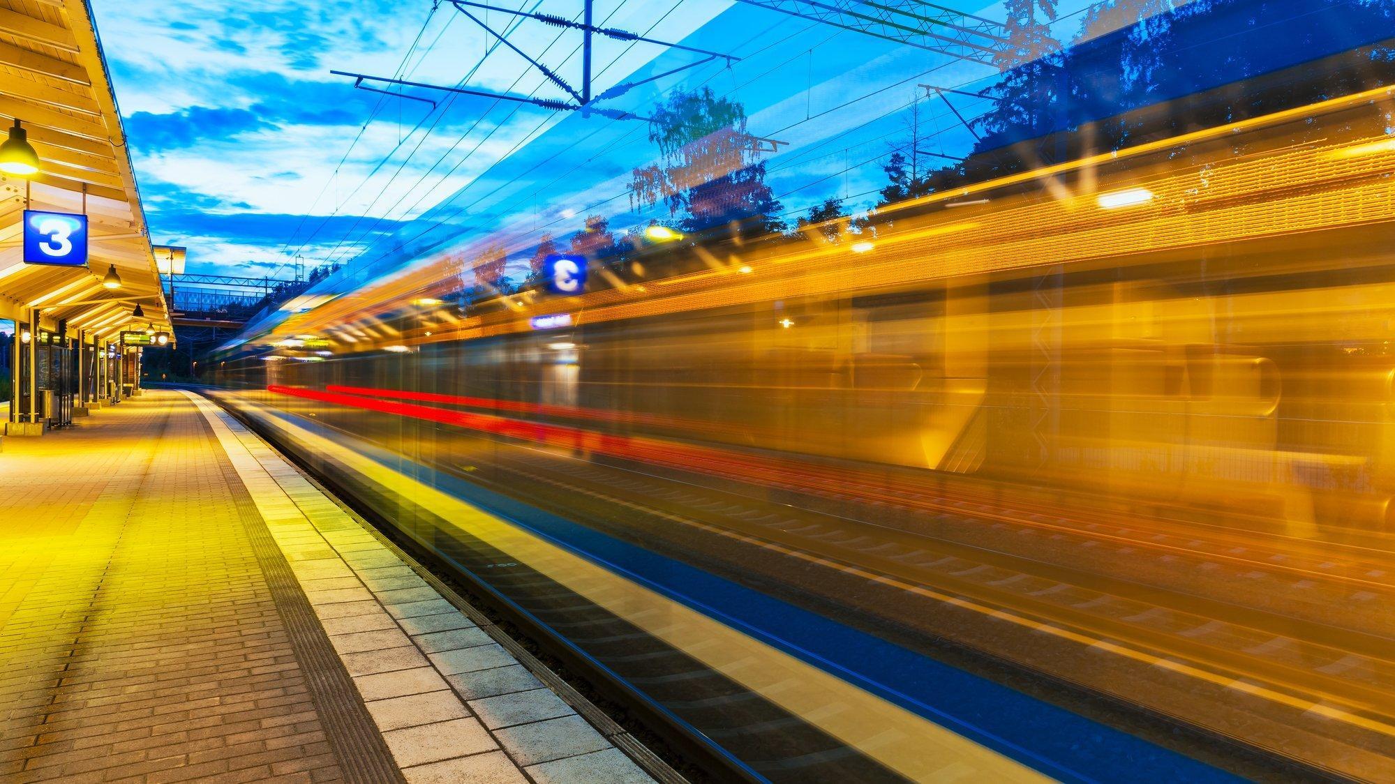 Ein Zug fährt Abends vom Bahnhof ab. Die Belichtungszeit ist hoch, darum ist der Zug geisterhaft zu erkennen und seine Beleuchtung zieht nach.