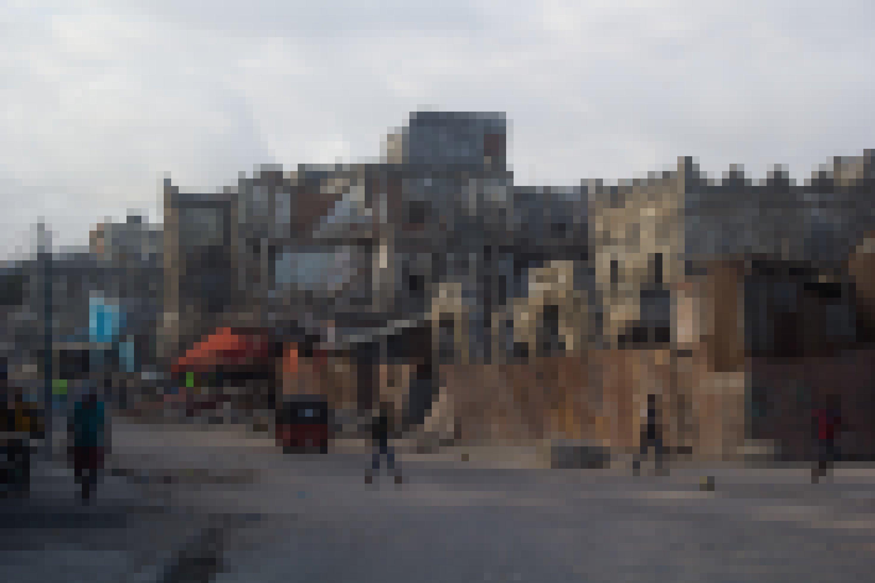 Zu sehen ist eine breite Straße, alle Gebäude am Rand sind zerstört. Auf der Straße vereinzelte motorisierte Dreiräder und Passanten.