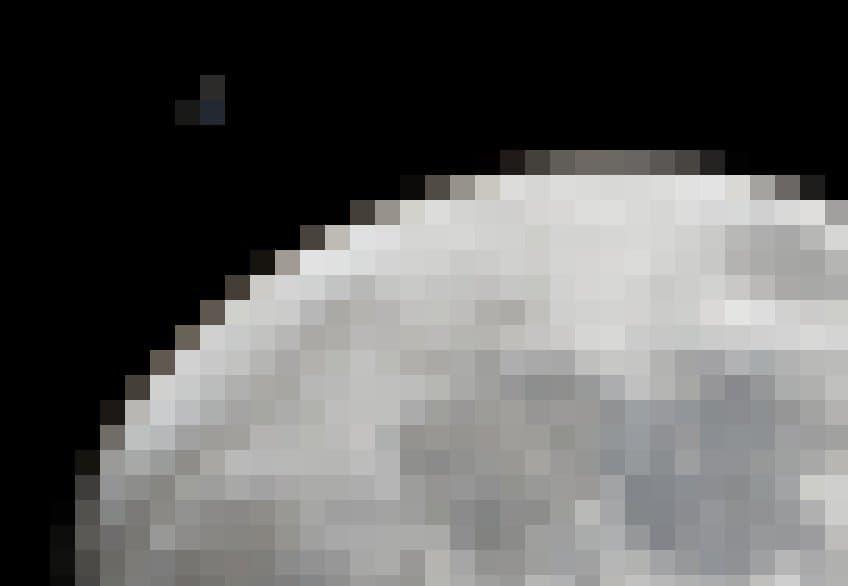 Eine große angeschnittene Mondscheibe, knapp daneben winzig klein die Internationale Raumstation, mit gerade so erkennbaren Solarzellen und Modulen. Das Bild wurde vom Erdboden aus aufgenommen – natürlich sind Station und Erdtrabant weit voneinander entfernt.