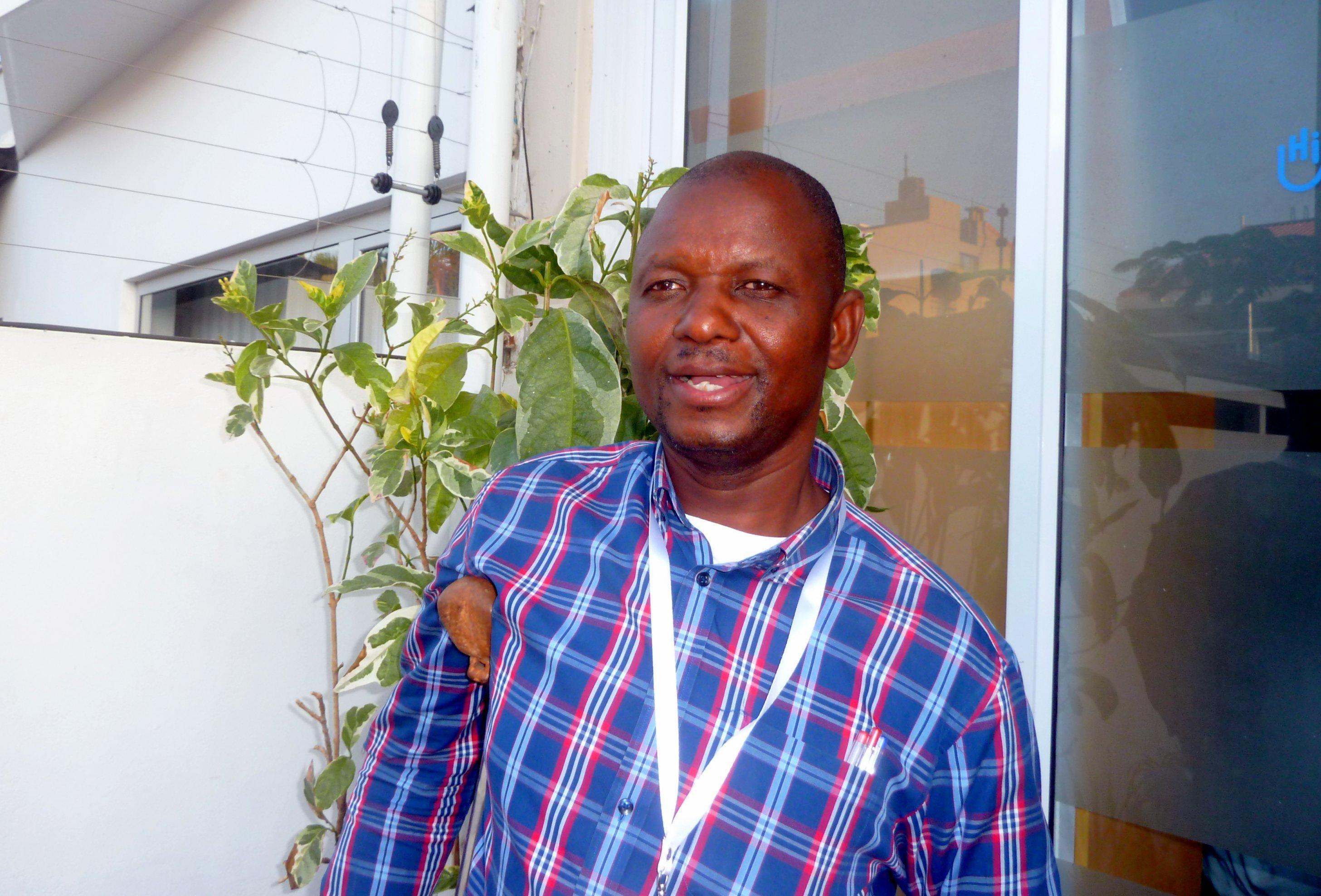 Porträt von Antonio Nhantumbo, er steht etwas schief auf seine Gehhilfe gestützt