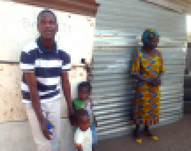 Dionisio, seine kleinen Geschwister und seine Mutter stehen vor ihrem Zuhause, die Fassade ist aus Wellblech