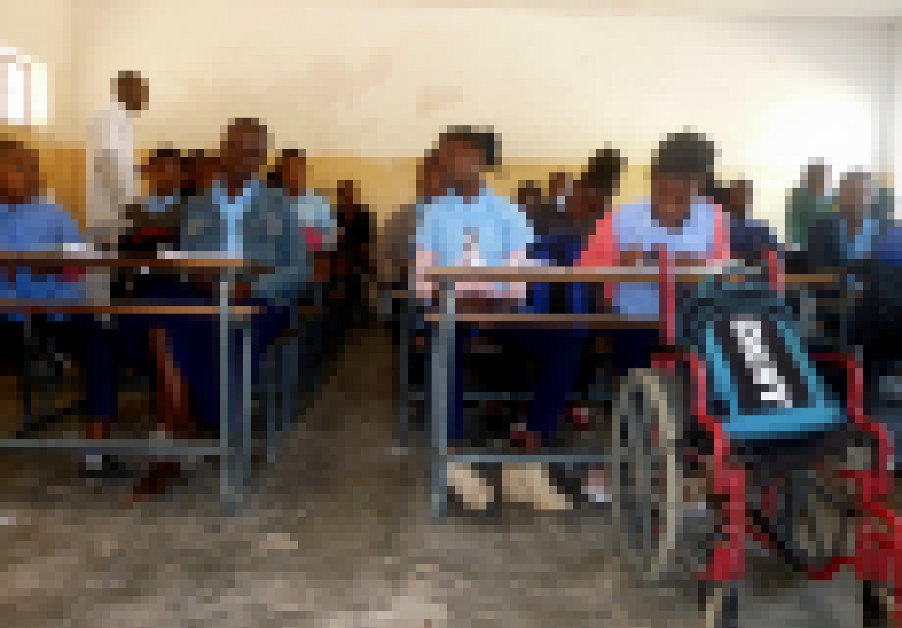 Chelsia sitzt im Klassenraum in der ersten Reihe und folgt konzentriert dem Unterricht, vor ihrem Holzpult parkt ihr Rollstuhl