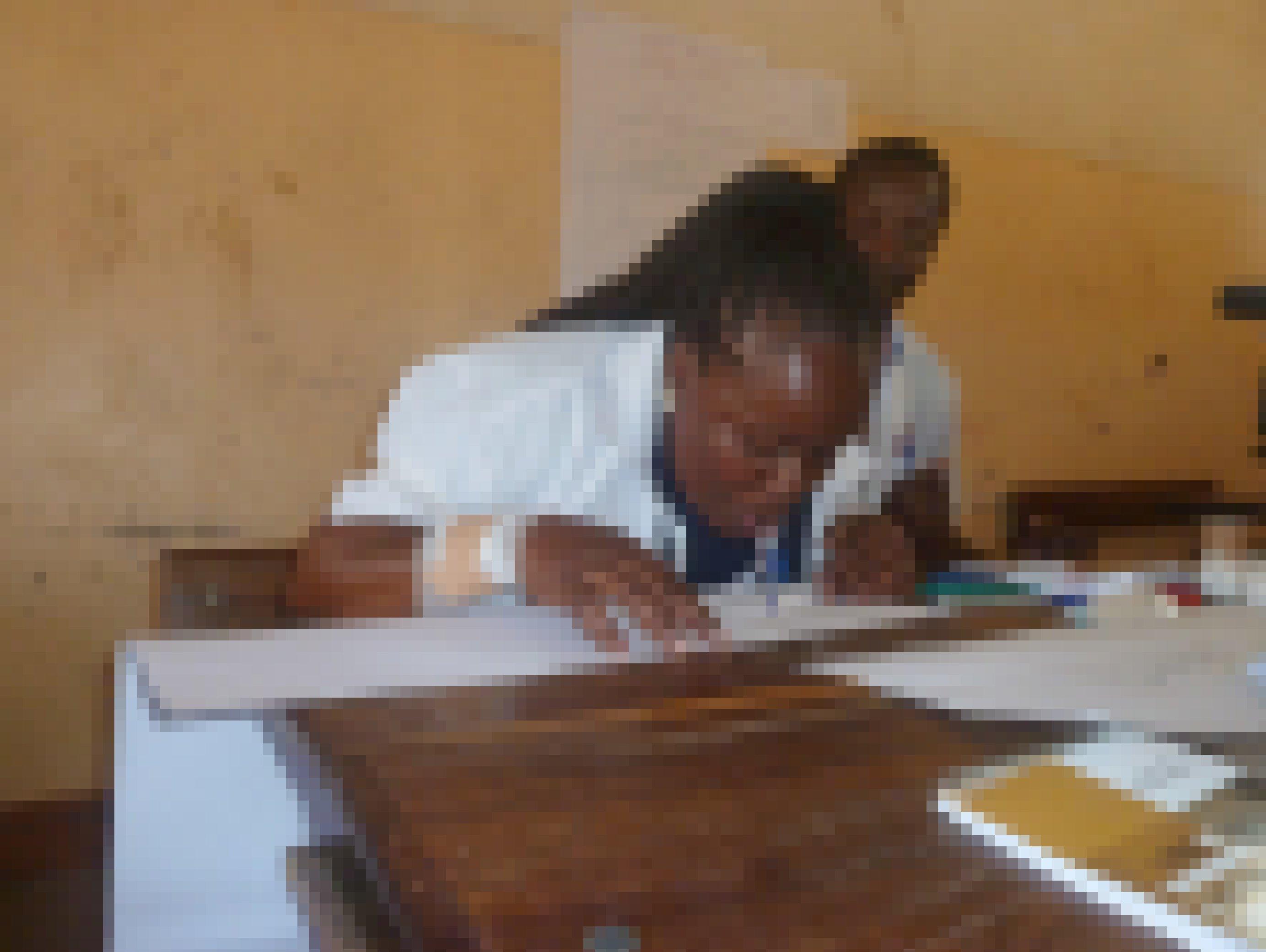 Die Lehrerin hat ihre Arme hochgebunden und einen Stift im Mund. Sie soll schreiben, ohne ihre Hände zu benutzen, um sich in die Lage von Schülern mit Behinderungen zu versetzen