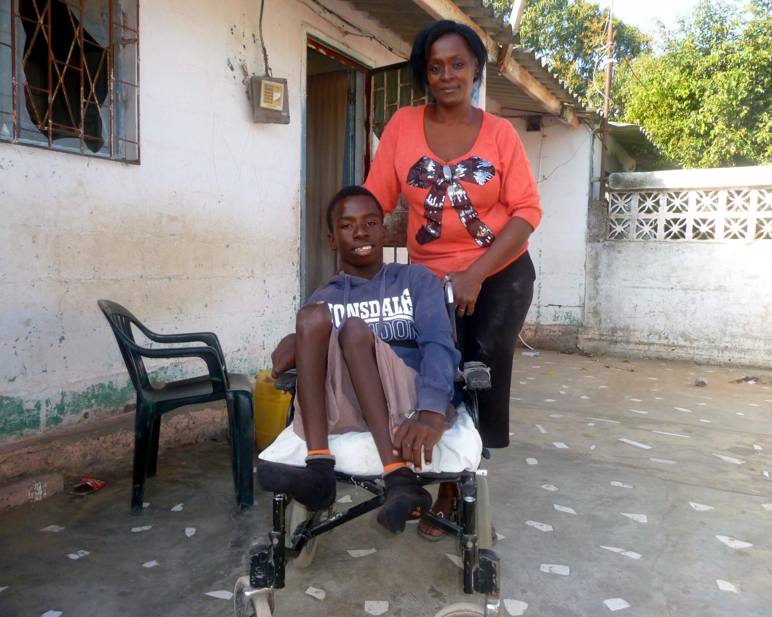 Mutter Maria Moinhe steht hinter ihrem Sohn Mario, der im Rollstuhl sitzt, die Beine hat er angewinkelt, beide lächeln in die Kamera