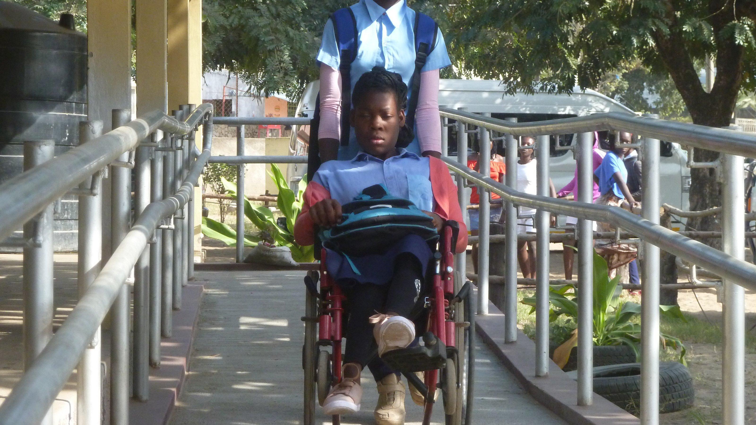 Chelsia sitzt im Rollstuhl, ihre Freundin schiebt sie die neue Rampe in der Schule hinunter, rechts und links ein Metallgeländer