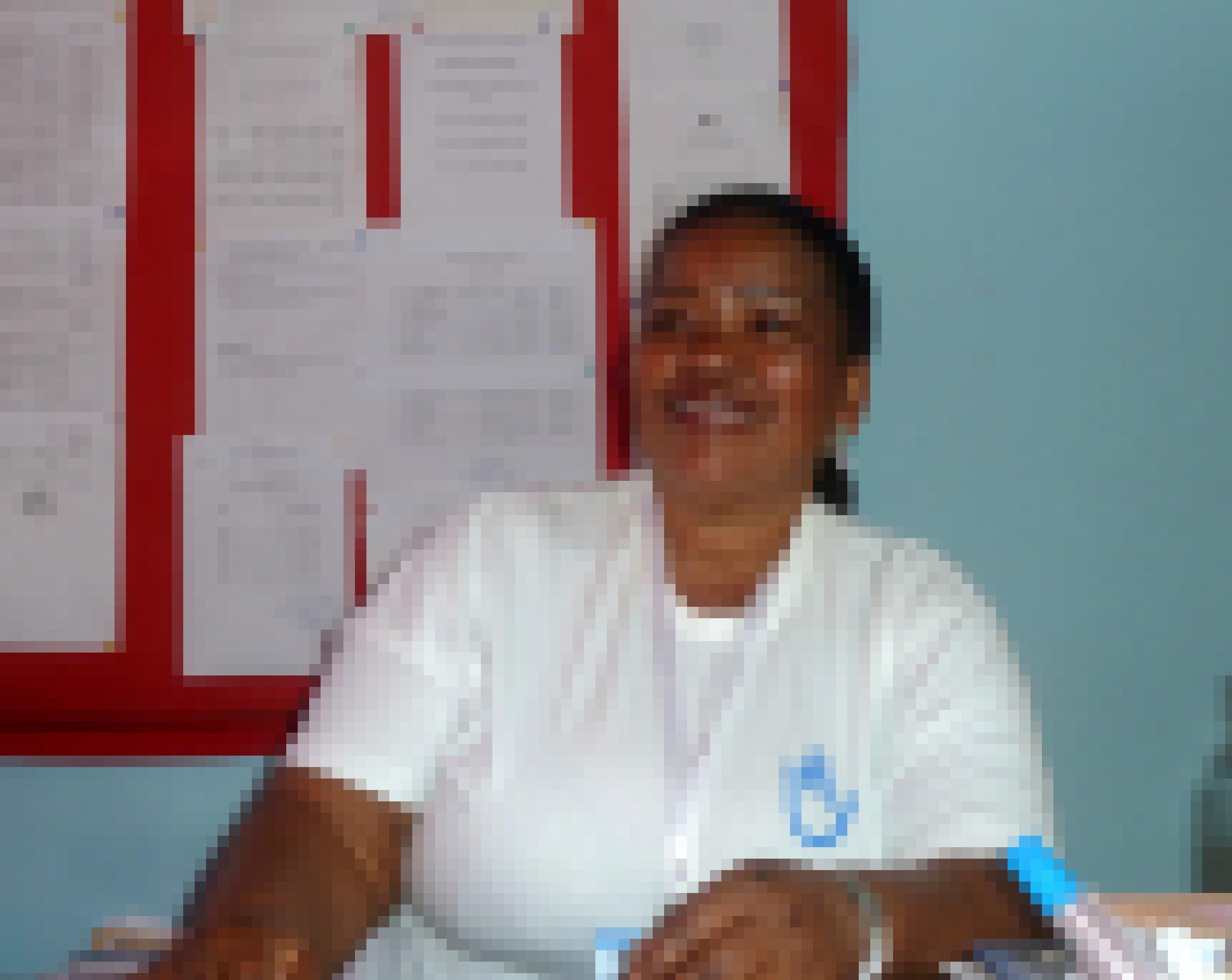 Schulleiterin Nelita Moises sitzt an ihrem Schreibtisch und lächelt herzlich in die Kamera