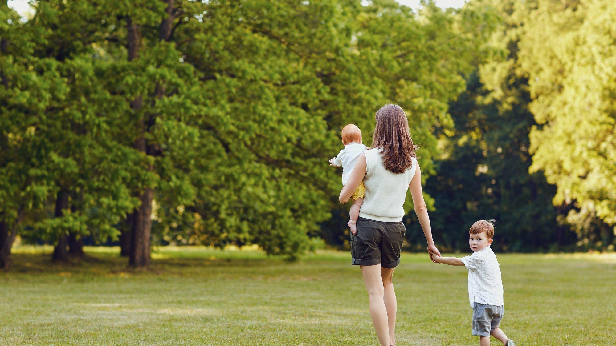 Eine junge Mutter geht mit ihren Kindern durch den Park. Ein Kind ist ein Säugling, den sie auf dem Arm trägt.