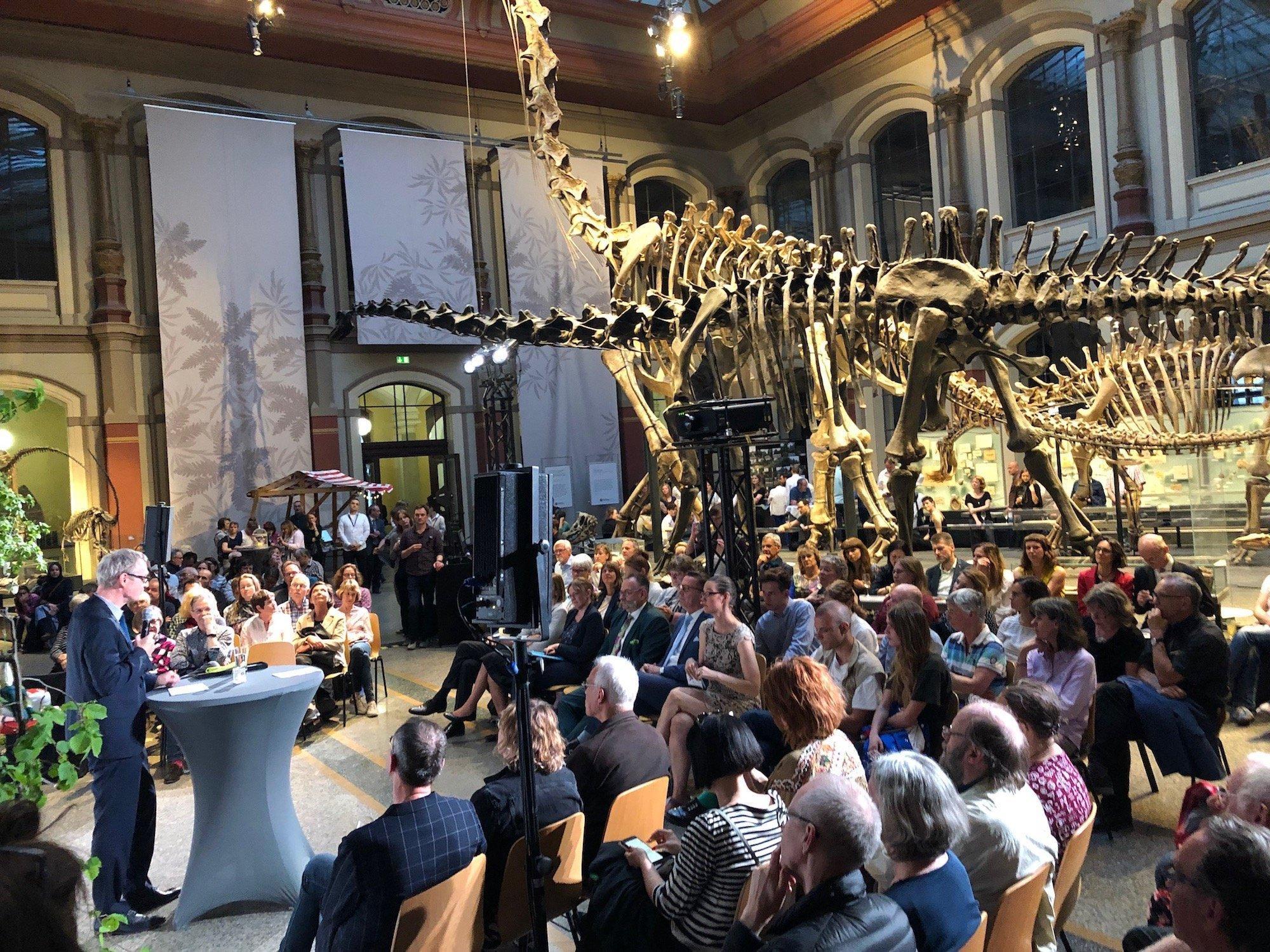 Viele Menschen sitzen um ein Redepult herum. Daran steht ein Mann im Anzug. Zwischen den Zuschauern befindet sich ein sehr großes Skelett eines Dinosauriers.