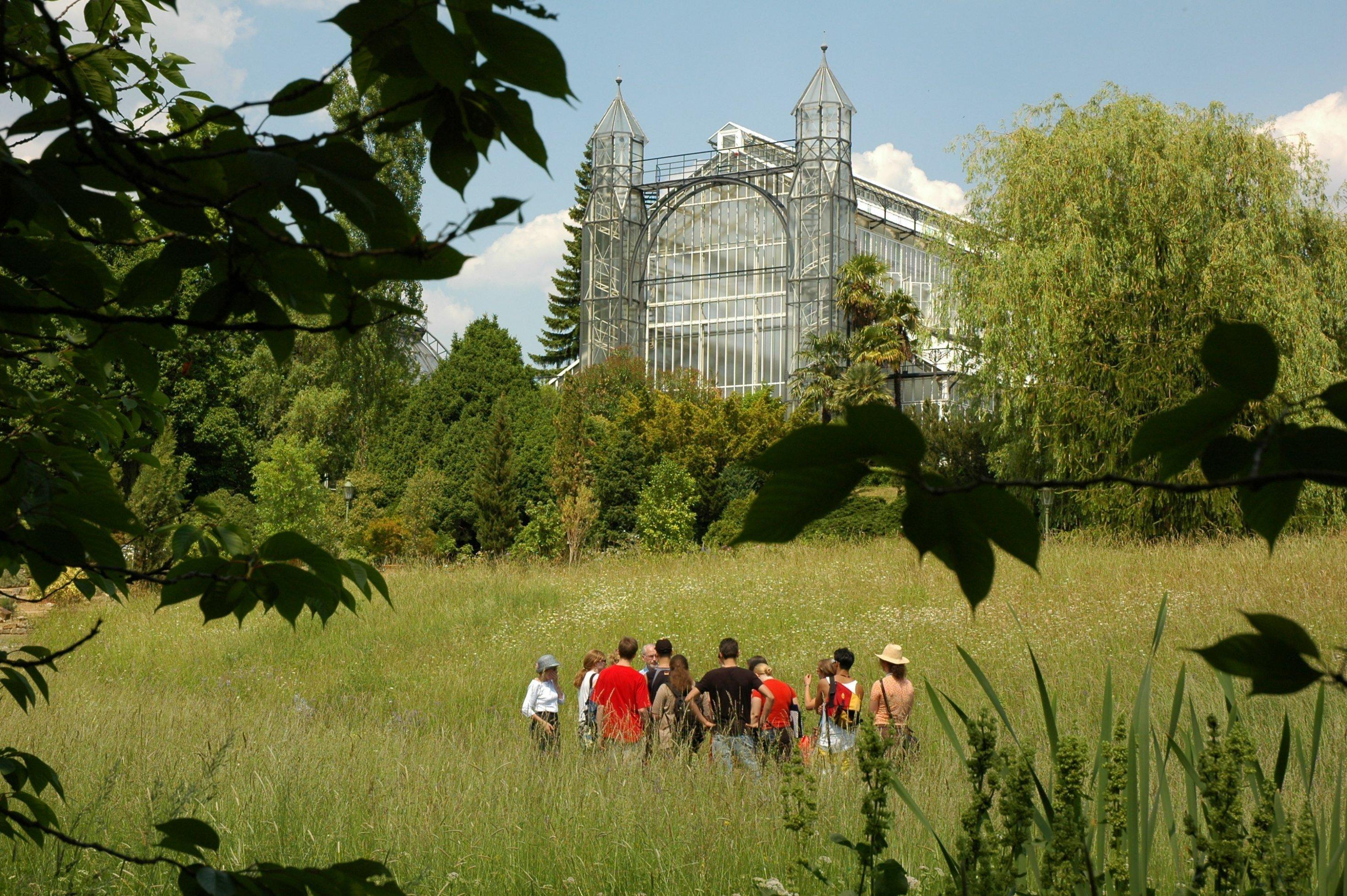Das Bild zeigt ein Treibhaus des Botanischen Gartens Berlin, das sogenannte Mittelmeerhaus, eingebettet in  die parkartige Landschaft. Dort steht eine Gruppe junger Menschen mit einem Dozenten.