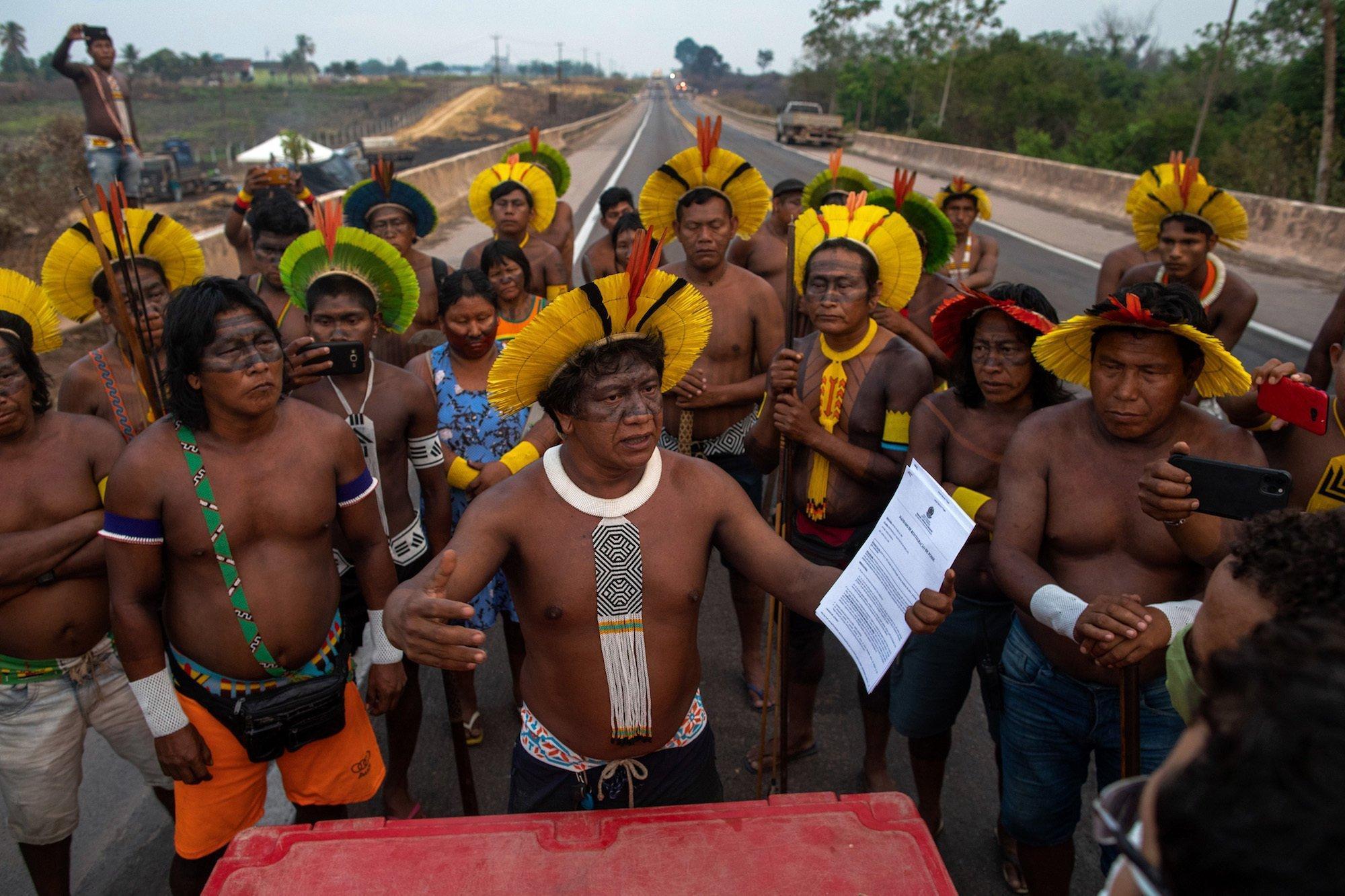 Angehörige des Stammes tragen Federschmuck und traditionelle Waffen bei sich, während sie mit nackten Oberkörpern mitten auf der blockierten Straße stehen. Der Anführer hält ein Dokument in der Hand, mit dem die Gruppe aufgefordert wird, die Blockade zu beenden.