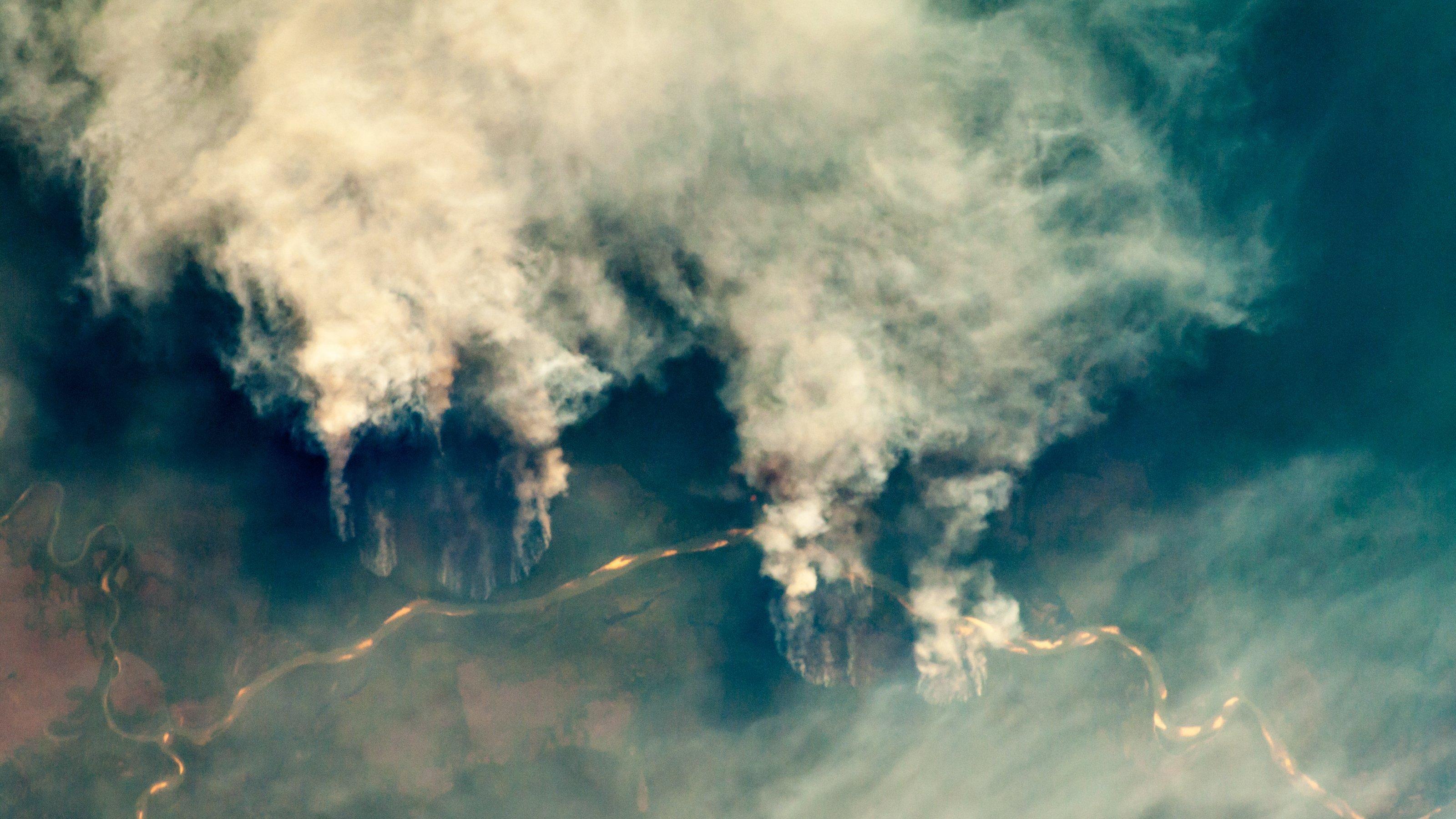 Satellitenaufnahme von brennendem Regenwald, Rauchsäulen steigen in große Höhe auf