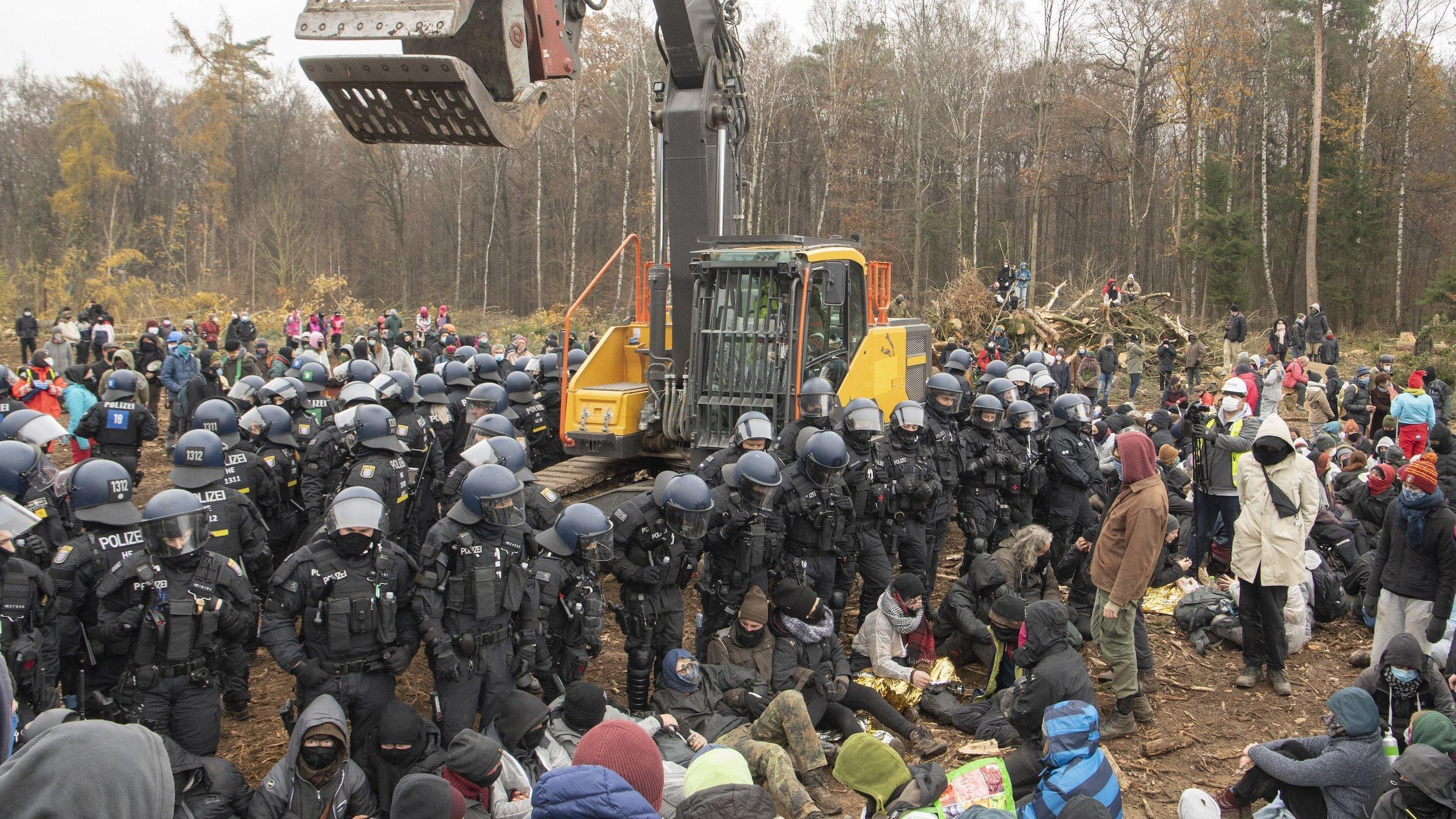 Der Dannenröder Forst soll einer Autobahn weichen. Aktivistînnen haben Ende 2020auf der Rodungsfläche im Wald einen Bagger blockiert. Polizistïnnen stellen sich ihnen entgegen.