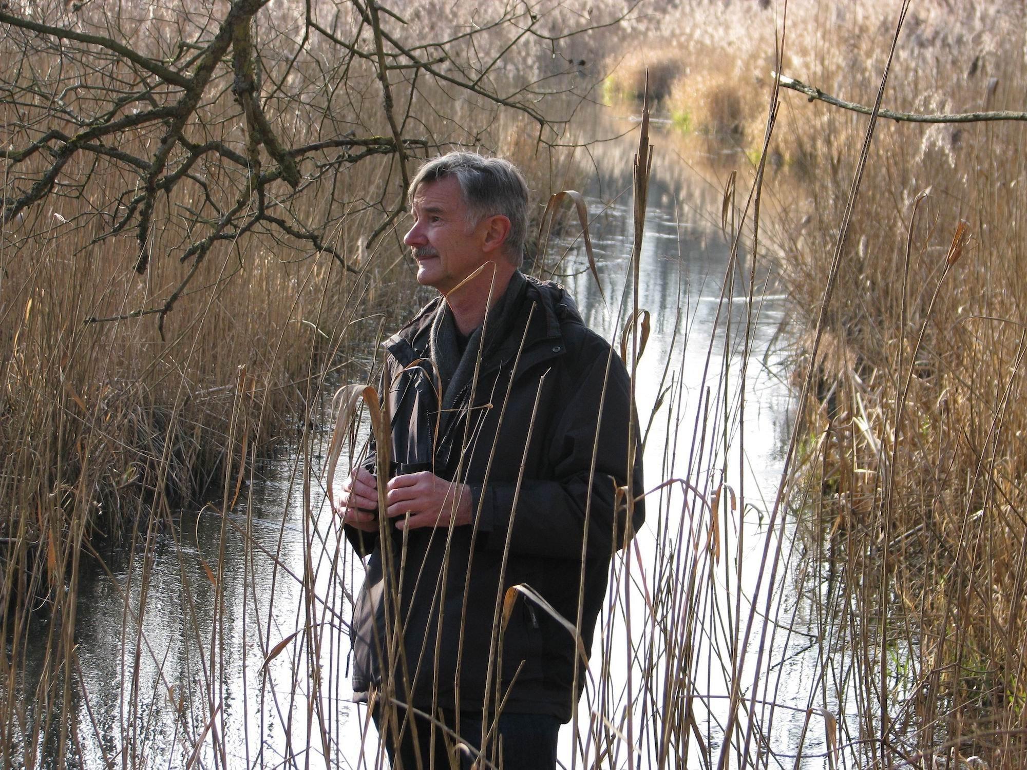Aufnahme des Biologen Josef H. Reichholf. Er steht zwischen Schilf an einem Bach.