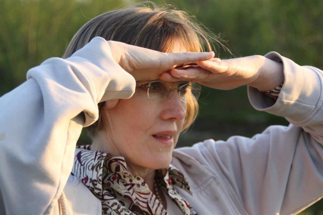 Foto von Johanna Romberg. Sie schützt ihre Augen mit ihren Händen vor der Sonne.