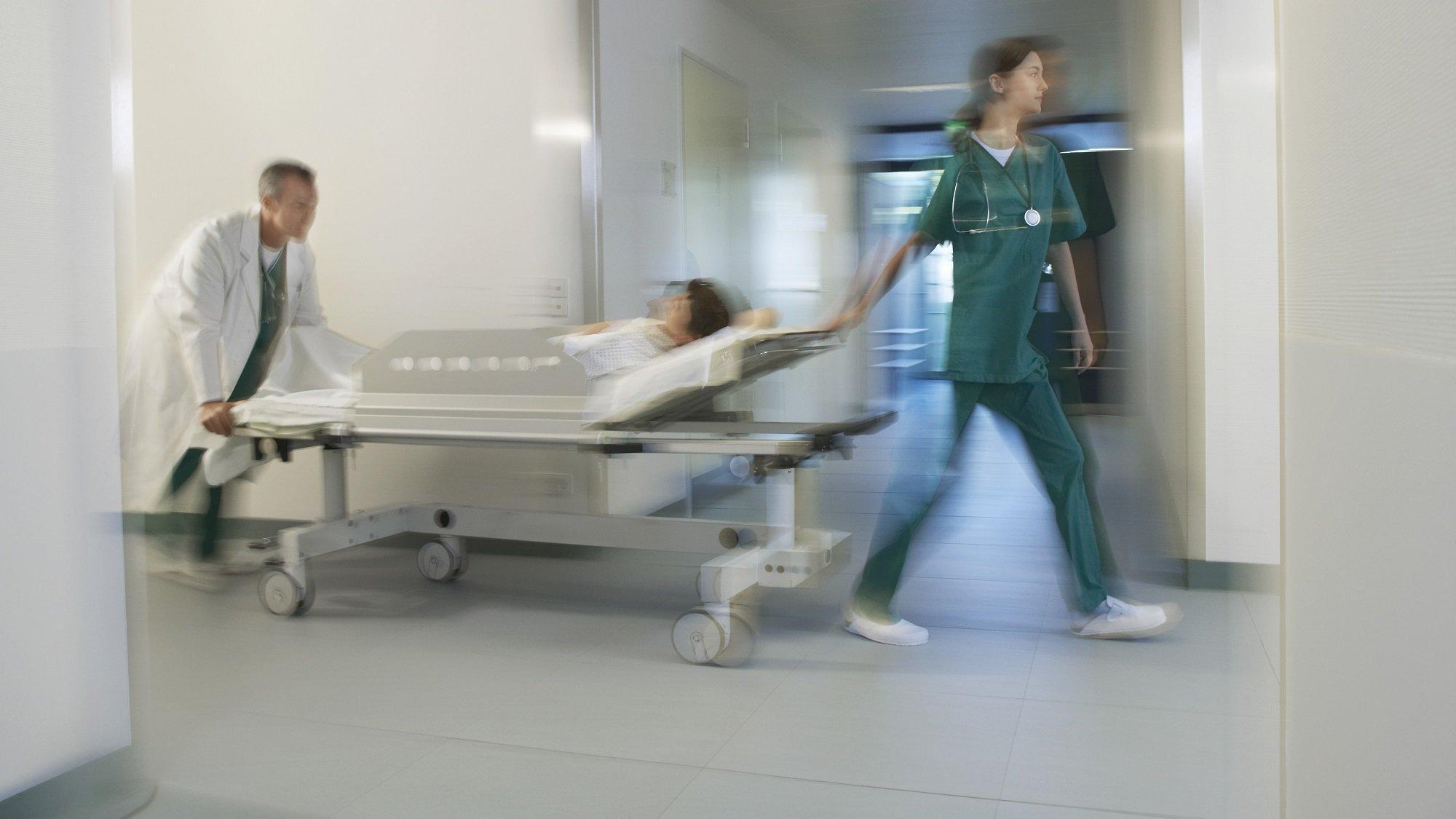 Ein Krankenpfleger schiebt einen Notfall-Patienten durch einen Krankenhausflur. Eine Pflegerein lenkt vorne. Sie haben es eilig.
