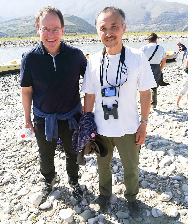 Zwei Forscher stehen auf Schotter an einem Fluss und schauen in die Kamera. Der rechte Mann hat einen Fotoapparat und ein Fernglas vor der Brust hängen.