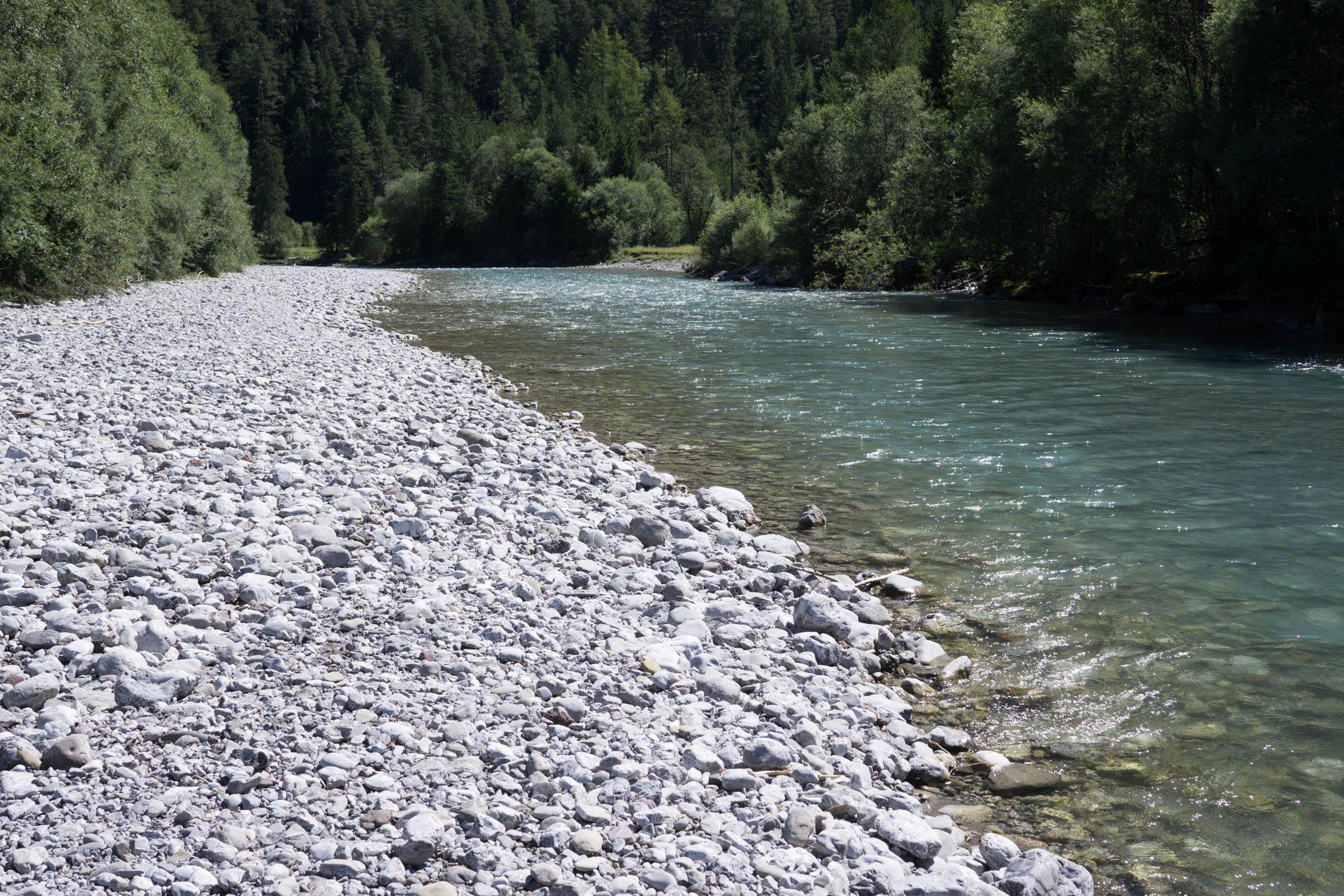 Ein türkisblauer Gebirgsbach fließt zwischen Bäumen, links erstreckt sich eine weiße Schotterbank, im Hintergrund sieht man einen Berg.