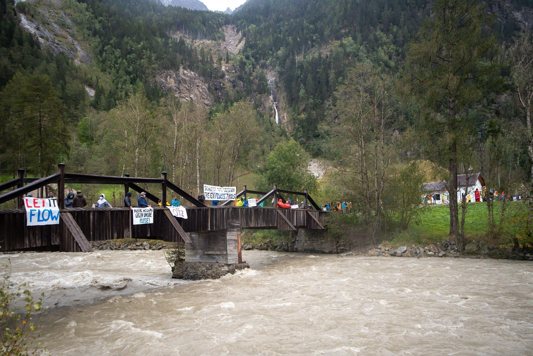 Ein Berg mit einem herunter stürzenden Bach im Hintergrund, vorne eine Holzbrücke über die Ache mit protestierenden Menschen.