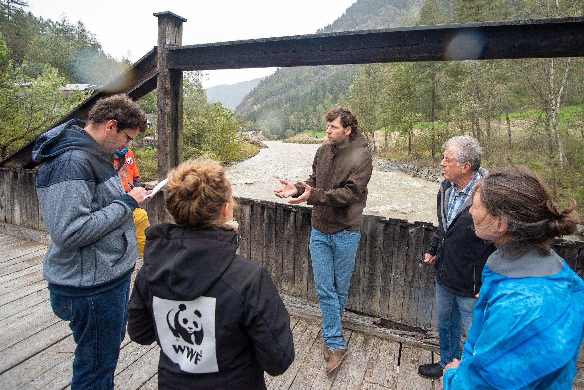 Menschen stehen auf einer Holzbrücke über einen reissenden Gebirgsbach und reden.