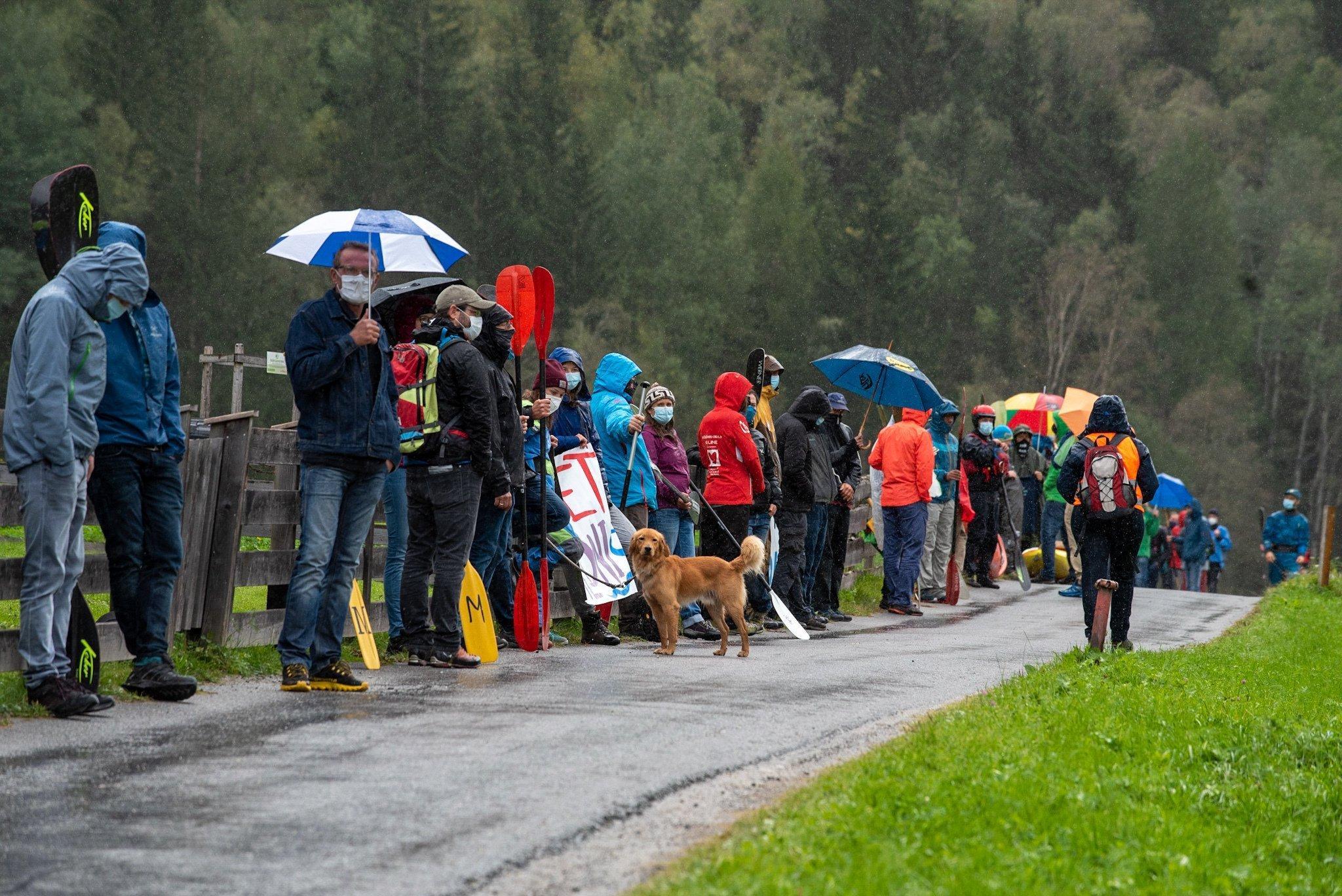 Eine Menschenkette im Regen an einer Straße.
