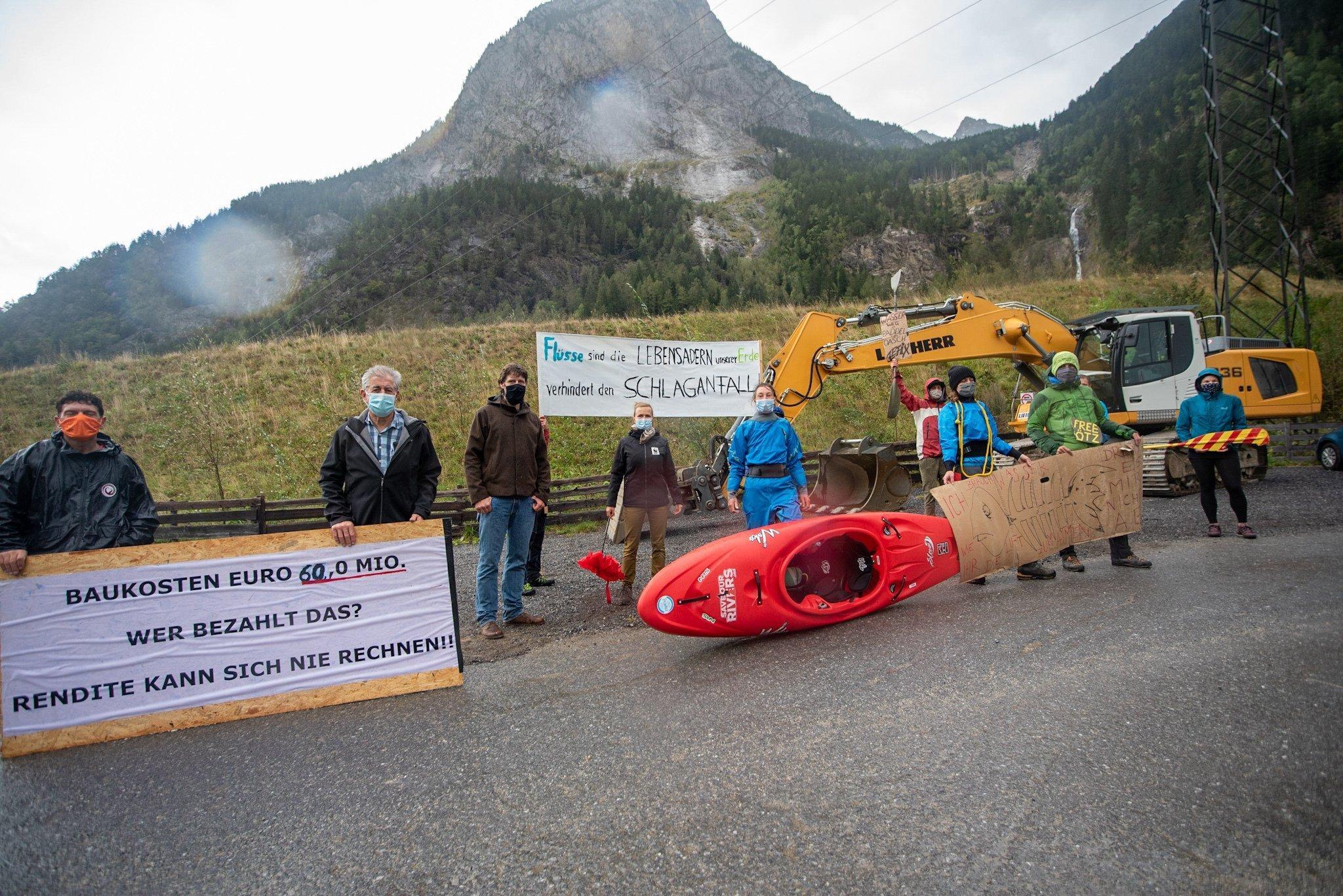 Menschen stehen mit Kajakbooten und Bannern im Regen an einer Baustelle.