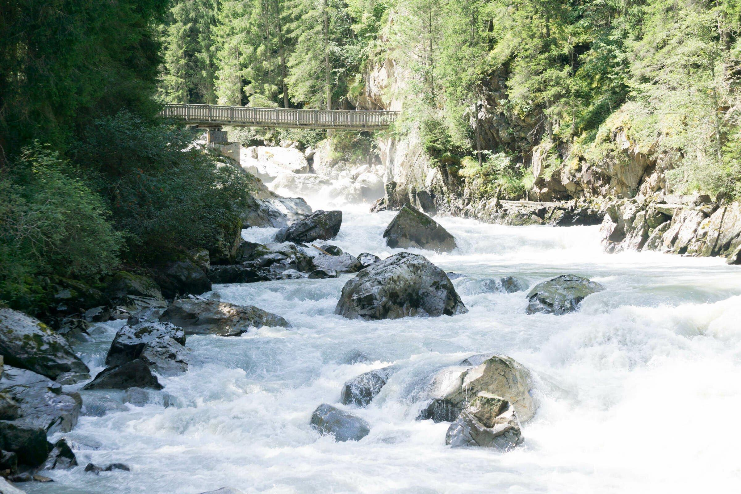 Tosender Gebirgsbach mit großen Steinen und eine Holzbrück.