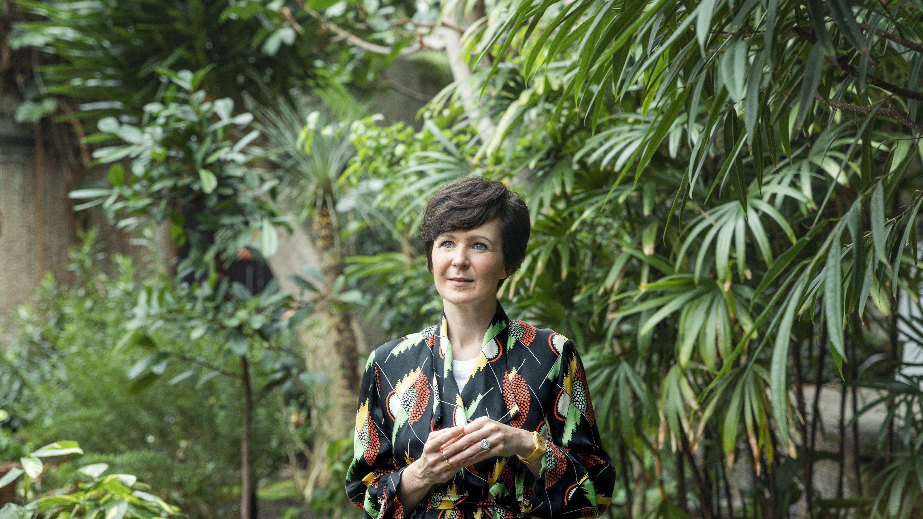 Foto von Olivia Laing. Eine Frau mit dunklen, halblangen Haaren steht vor einer großen Grünpflanze.