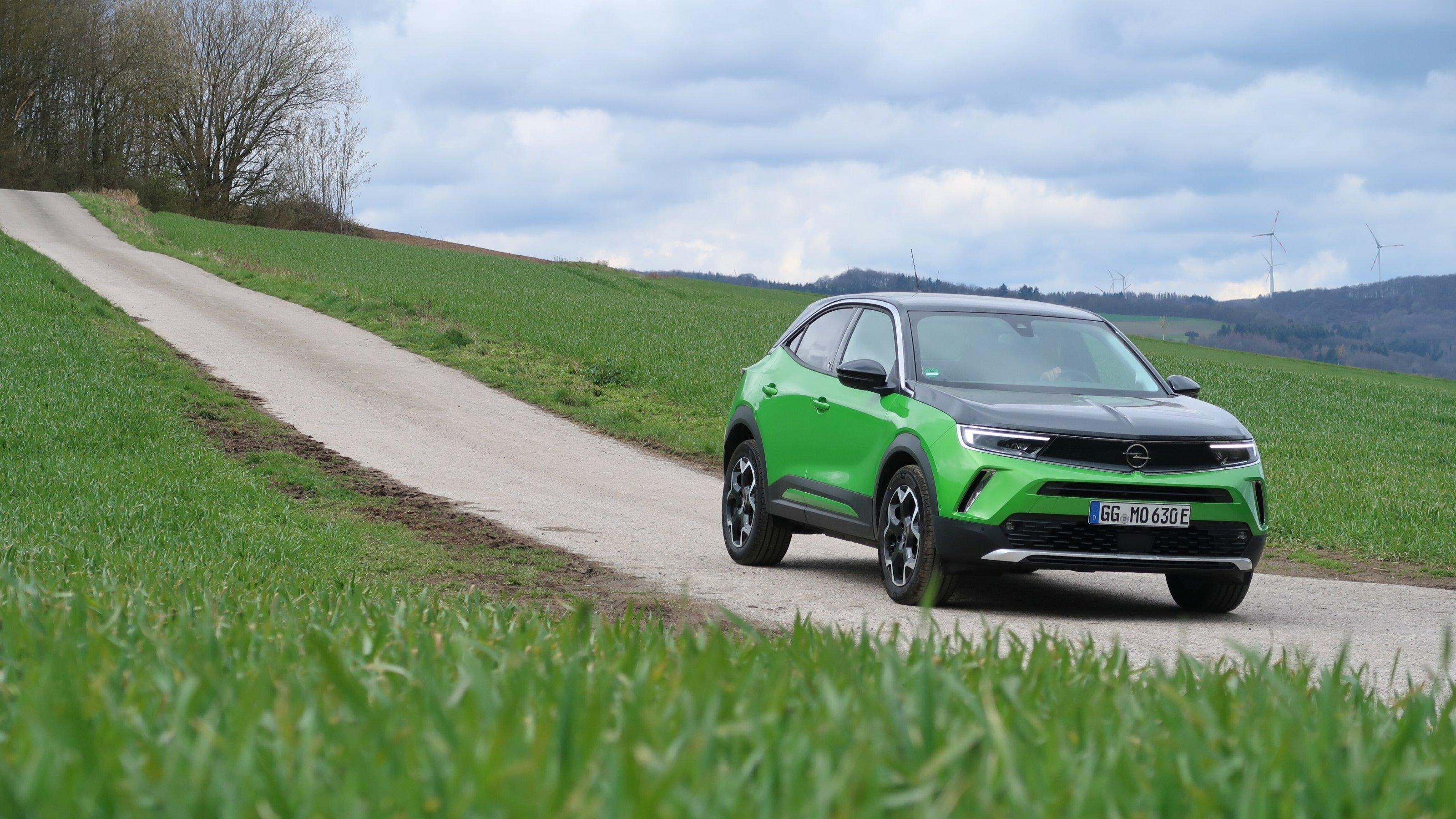 Ein Opel Mokka fährt einen Feldweg runter.