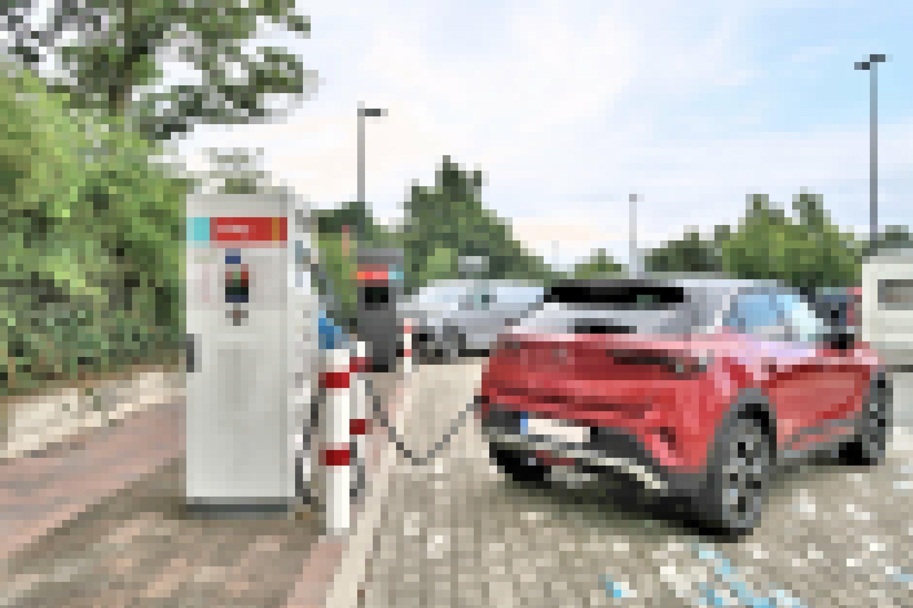 Ein roter Opel Mokka-E ist an einer Ladestation auf einem Parkplatz angeschlossen.