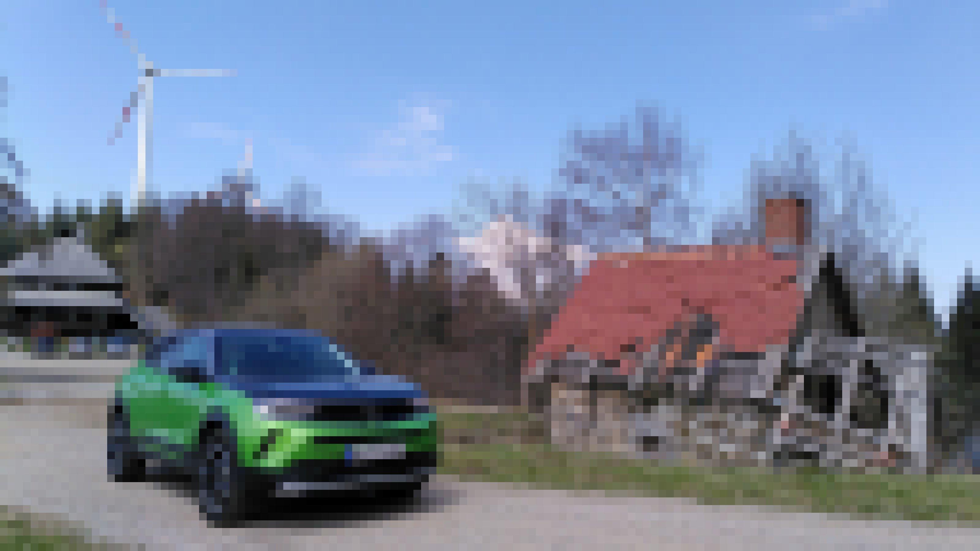 Ein Auto steht vor einer verfallenen Holzhütte. Im Hintergrund ist ein Windrad zu sehen.