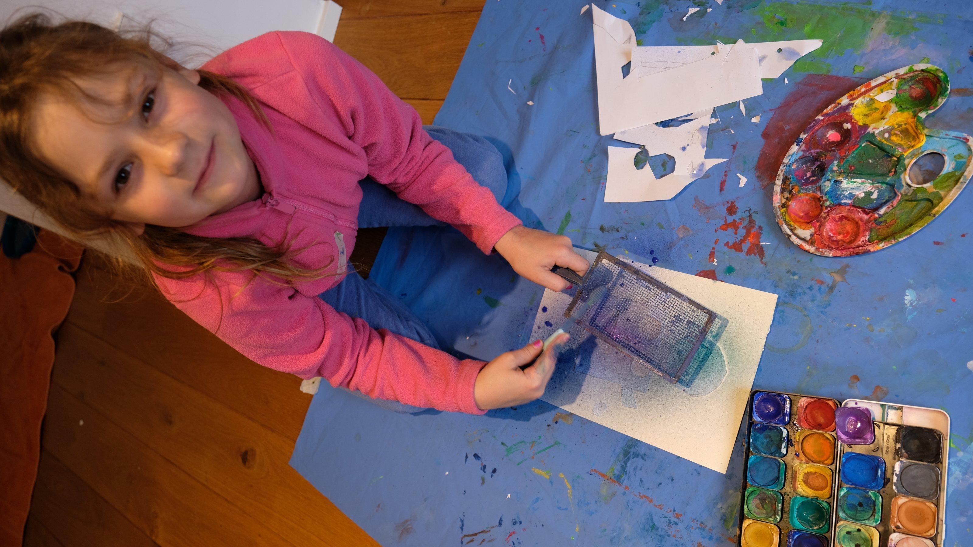 Auf einer blauen Wachstischdecke hockt die achtjährige Orla über ihrem Blatt Papier. Vor ihr liegen der Wasserfarbkasten und eine bunte Palette zum Farbenmischen. Sie guckt in die Kamera. Links hält sie ein Sieb, rechts eine Zahnbürste mit Farbe. Auf dem Papier sind schon ein paar Spritzer verteilt.