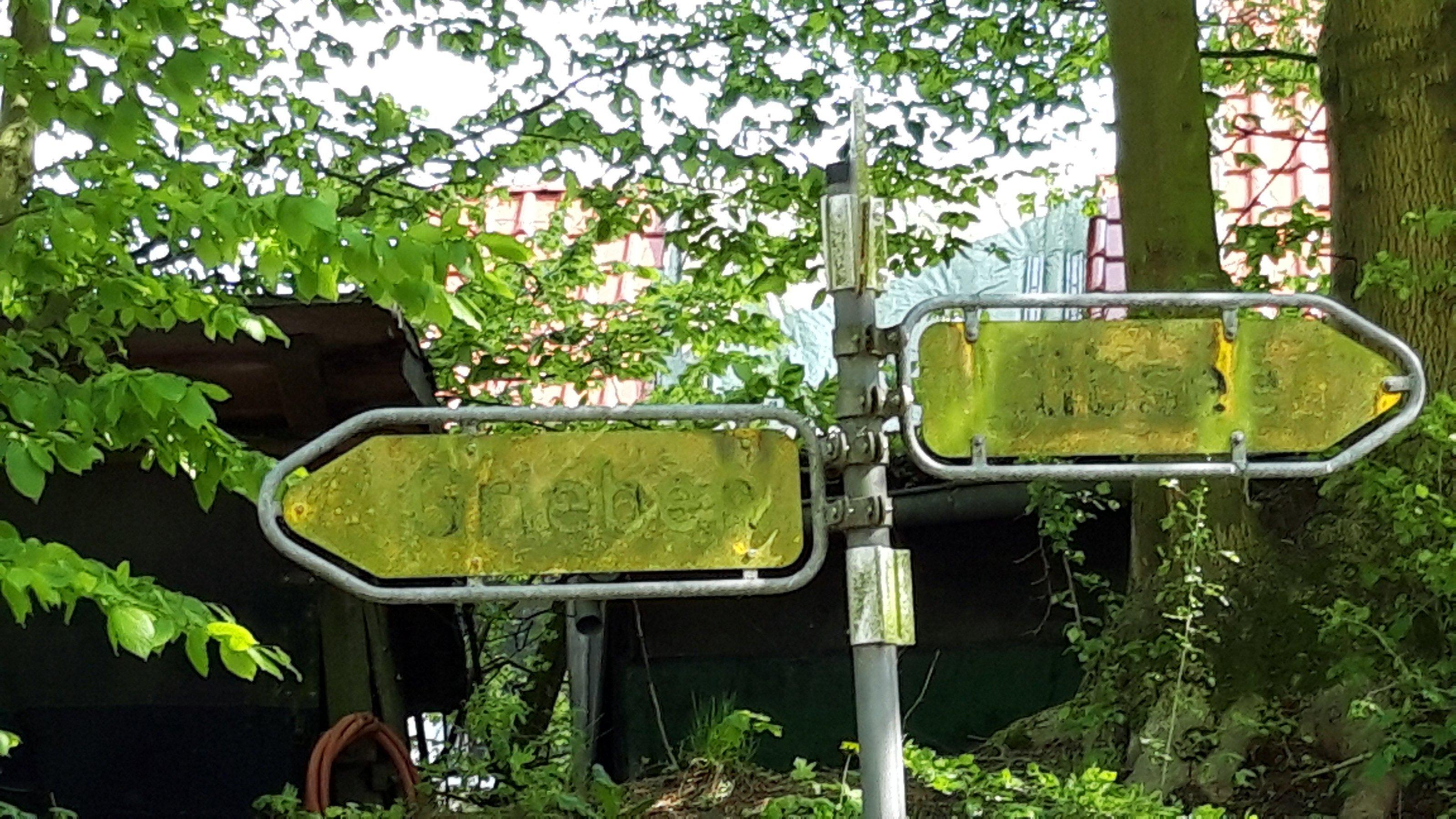 Vermooste Orts-Hinweisschilder im westlichen Mecklenburg.