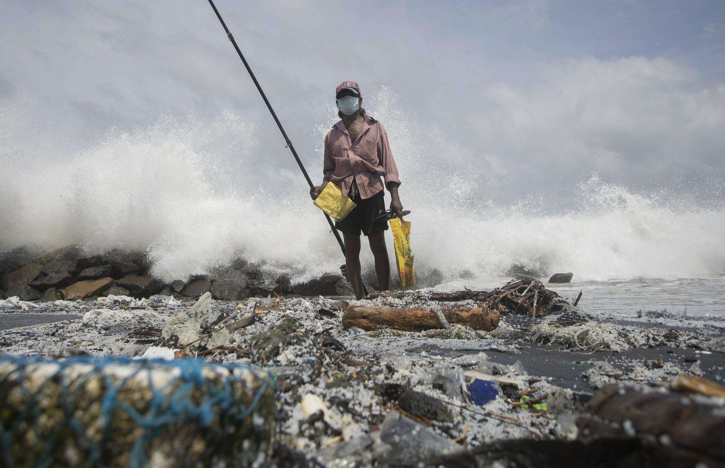 Fischer inmitten von Müll am Strand mit einer langen Angel in der Hand.