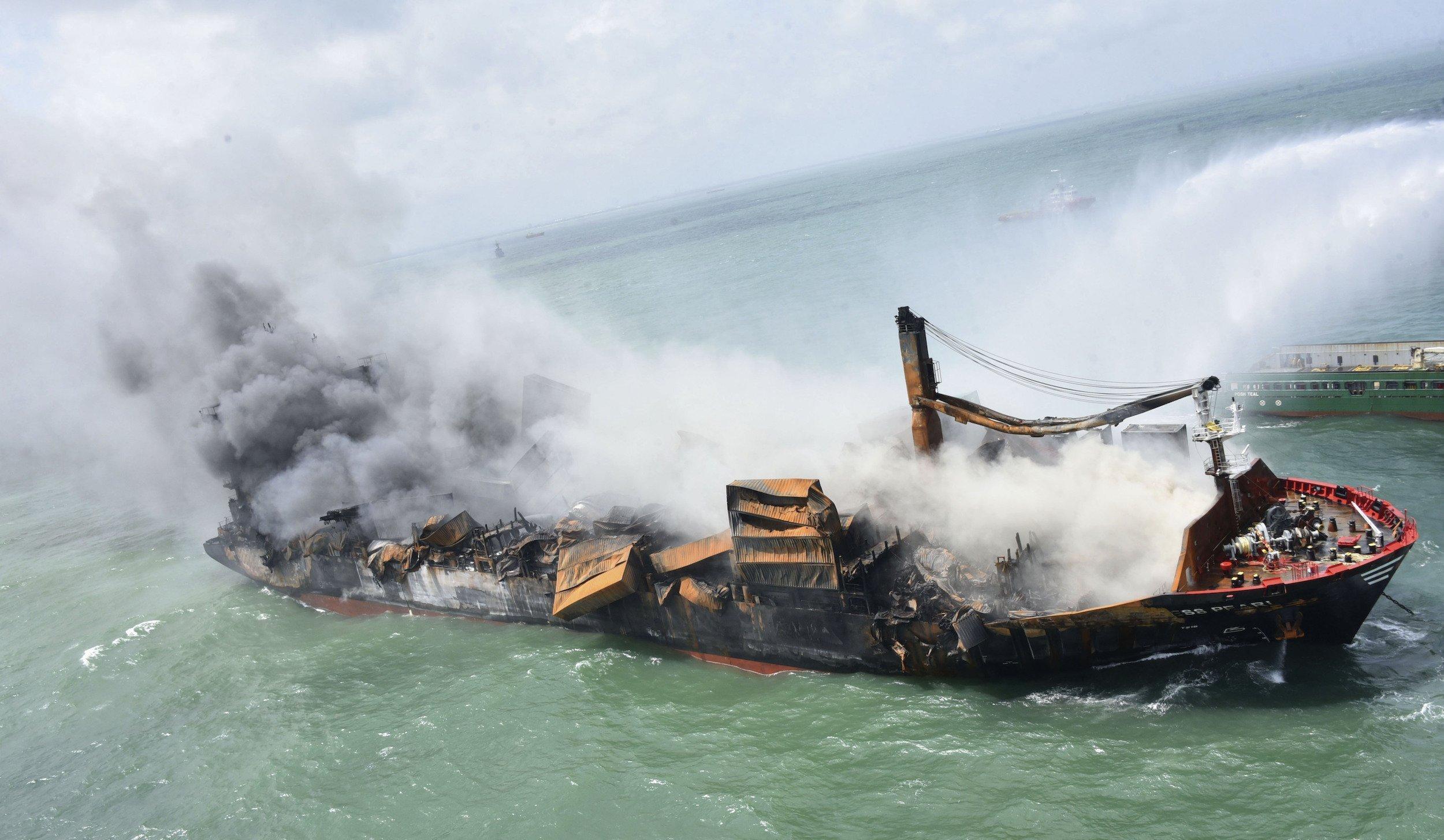 Ein sinkender, brennender Frachter, von rechts Wasser von einem Löschschiff.